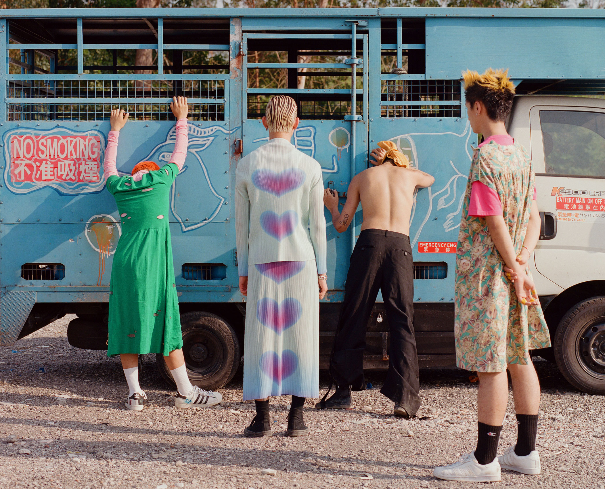 four boys wearing dresses stand with their backs to the camera, in front of an old pale blue truck