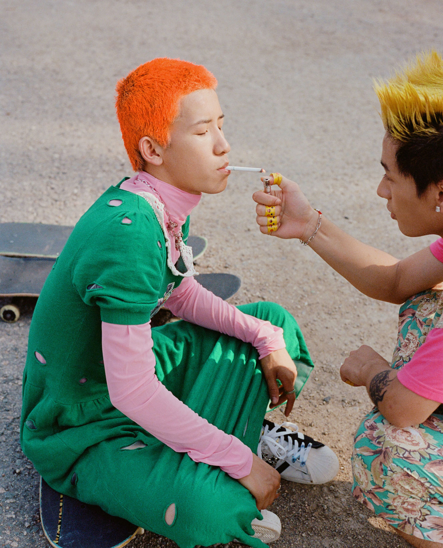 two young men with colourful hair sit on skateboards, one lights the other's cigarette
