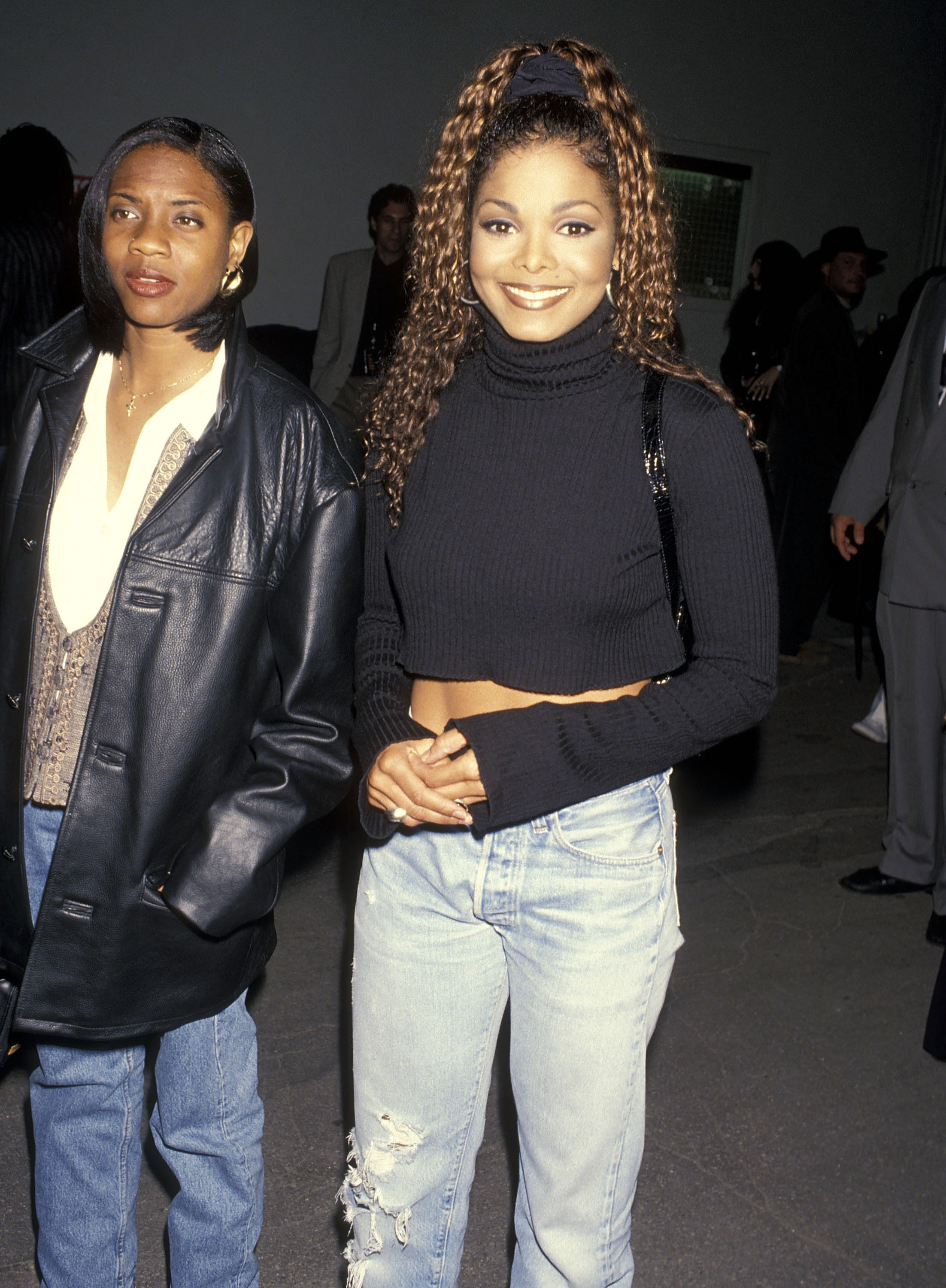 janet jackson in the street smiling at the camera in a turtleneck