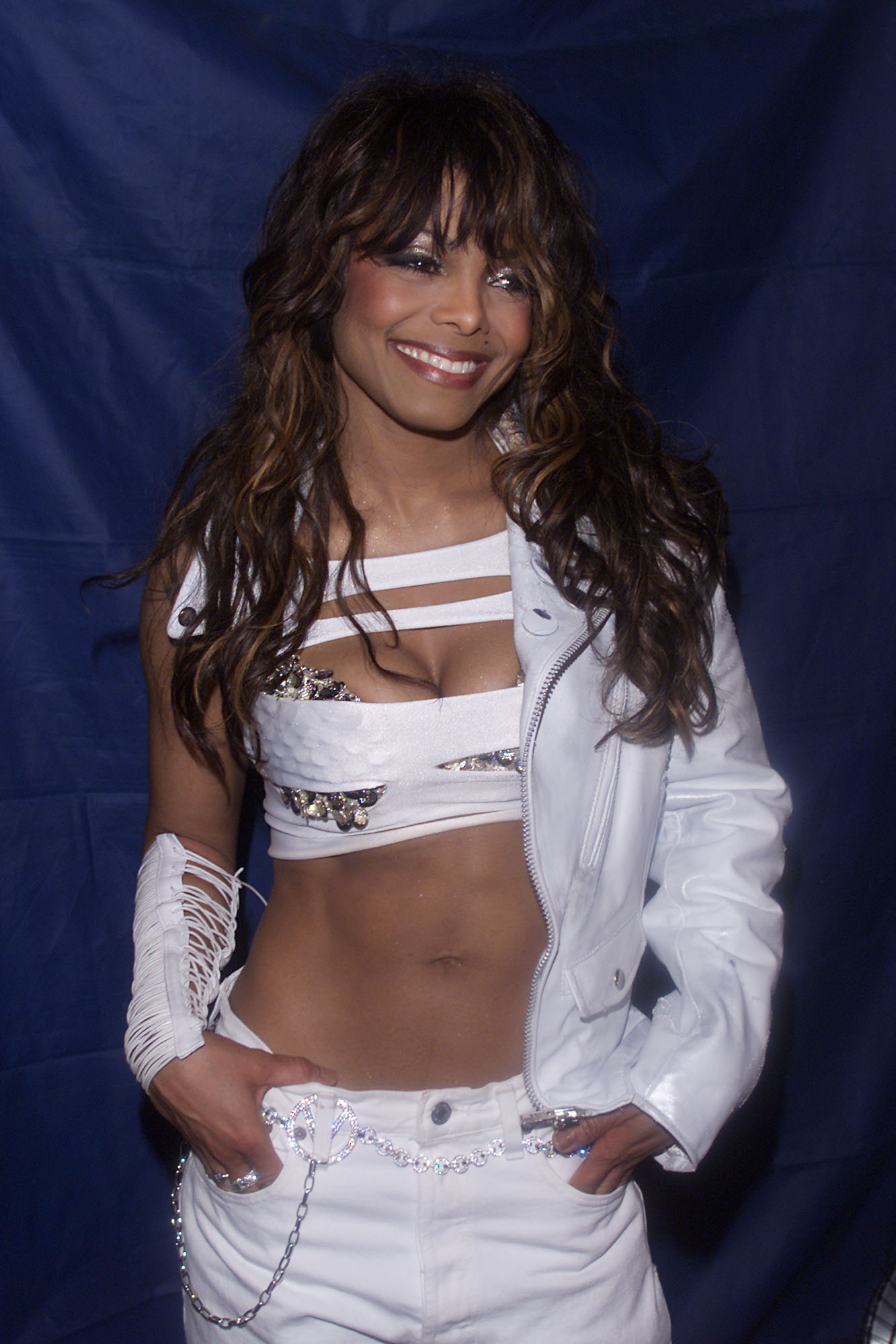 janet jackson standing with her hands in her pockets wearing a slashed crop top