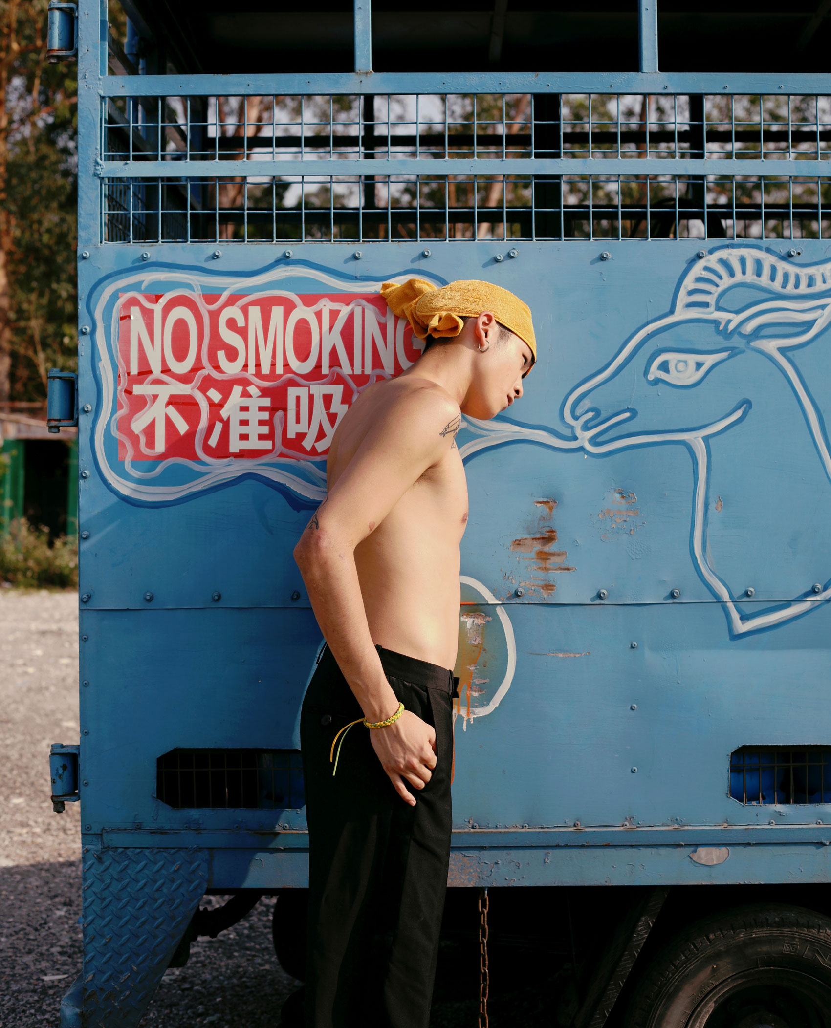 a young man wearing black trousers and a yellow headscarf leans sideways against an old blue truck