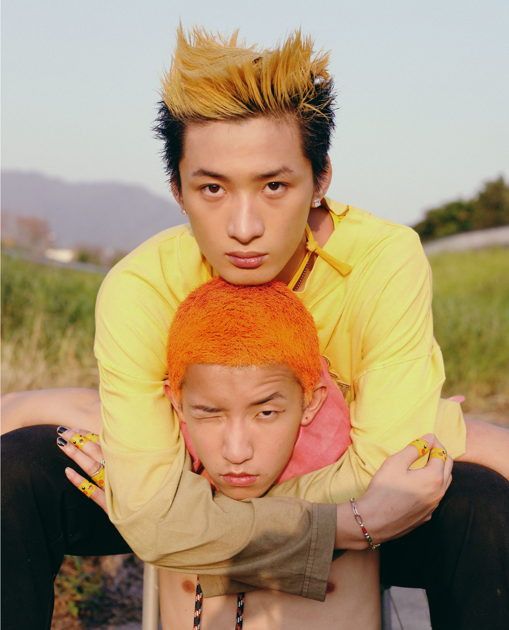 a young man with yellow hair sits behind a topless man with bright orange hair, wrapping his arms around him affectionately