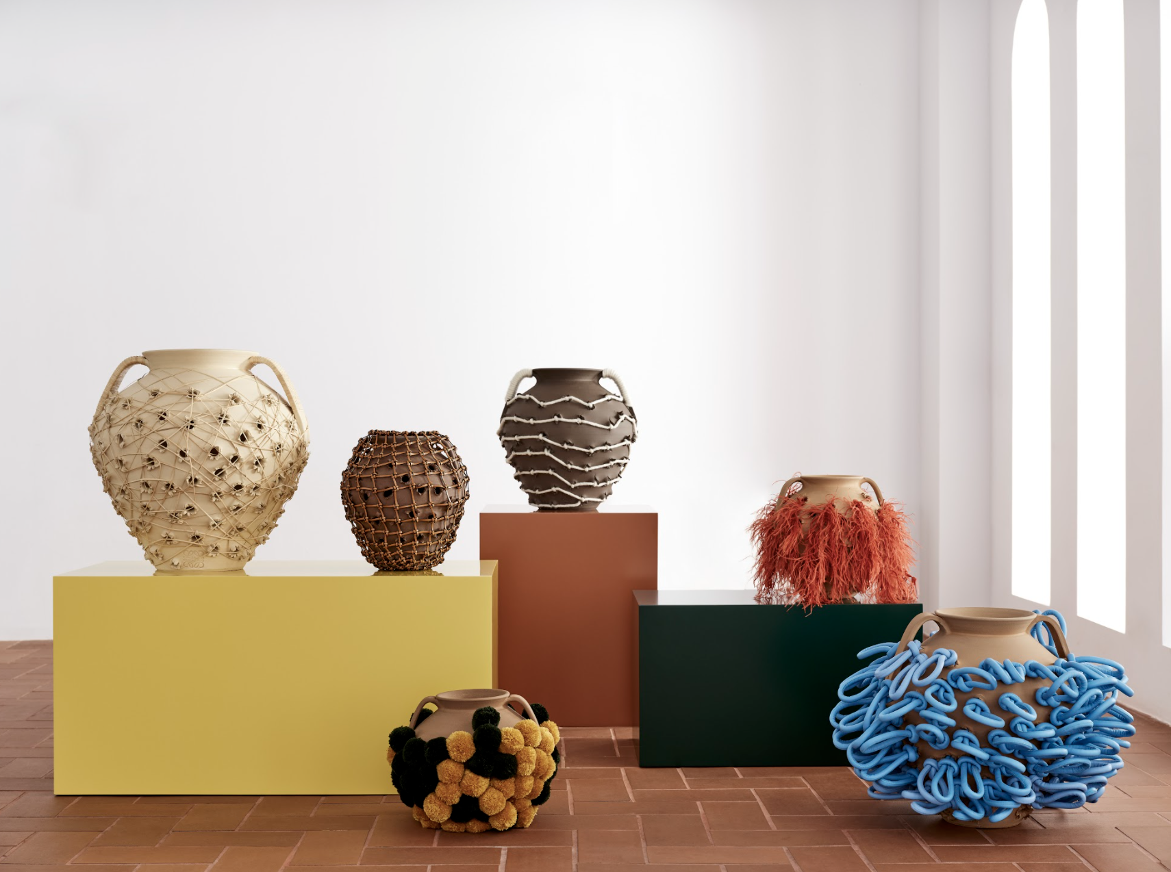 six abstract pots made from clay chestnut roasters, displayed on plinths
