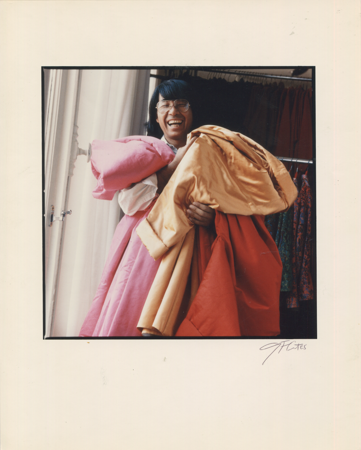 Kenzo Takada smiling, holding colourful looks