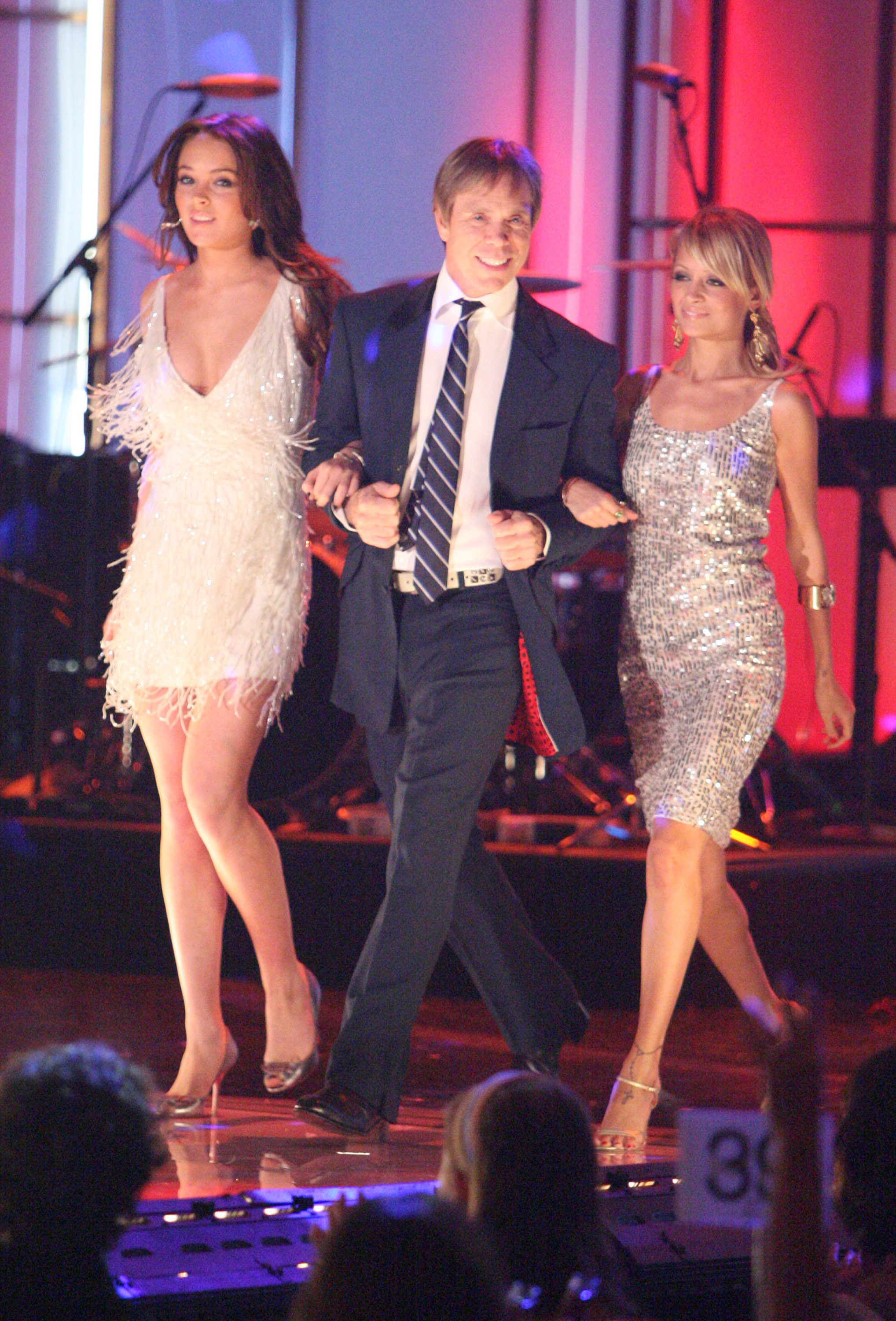 lindsay lohan, tommy hilfiger and nicole richie arm in arm walking on a stage