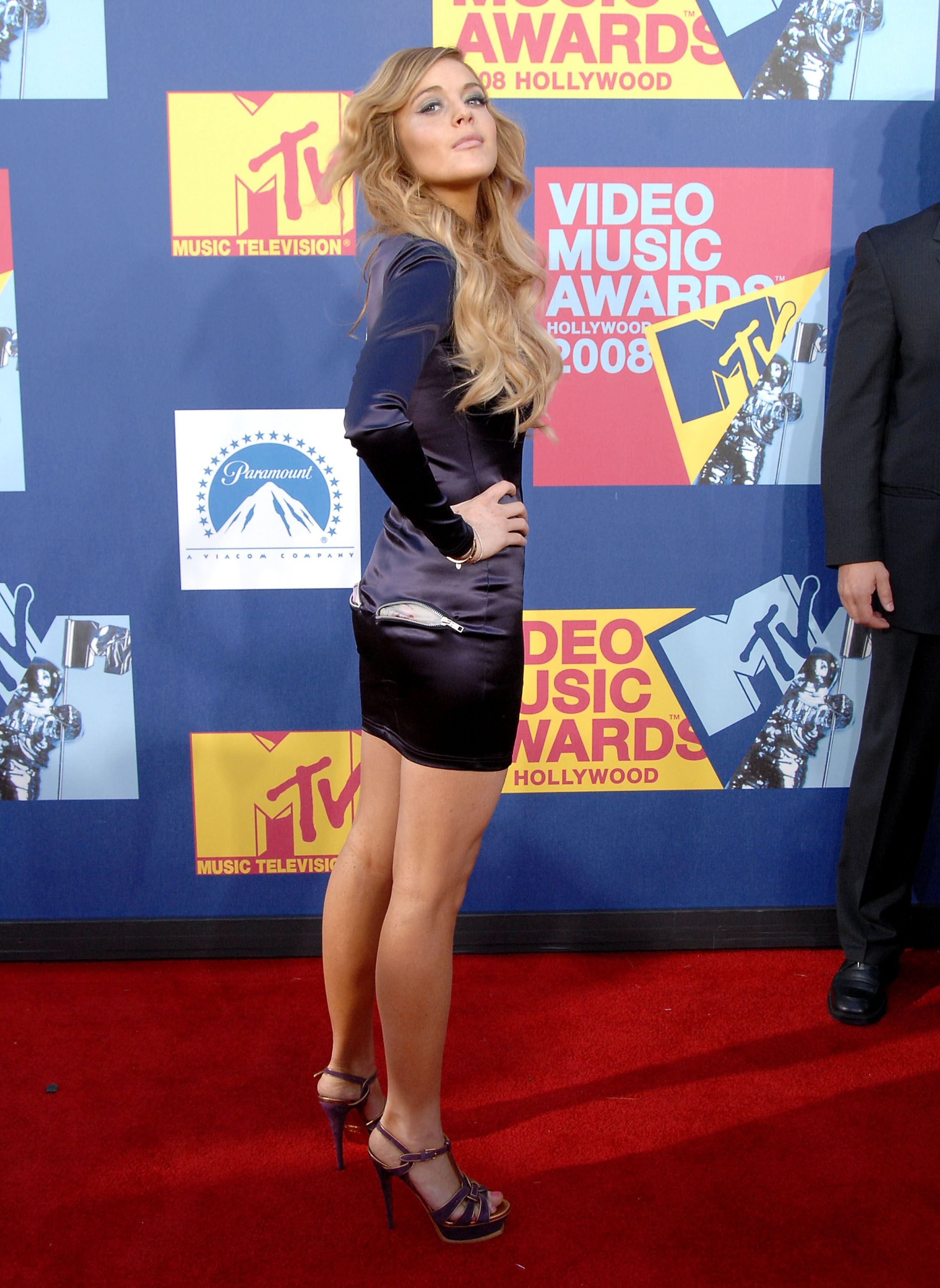 lindsay lohan standing with her hand on her hip on the vmas red carpet