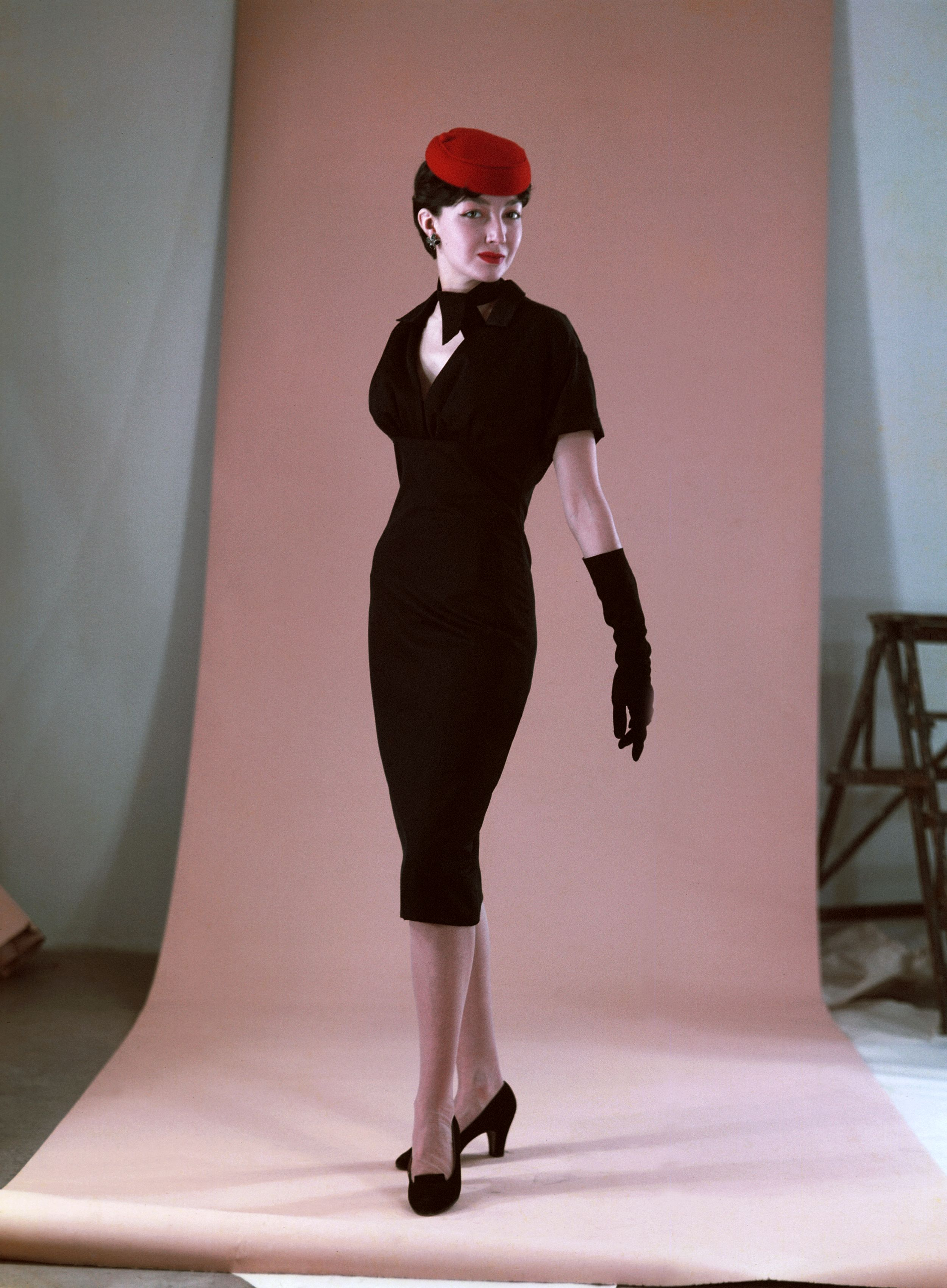 A woman wearing a fitted Black Dior Dress, shot against a light pink back drop