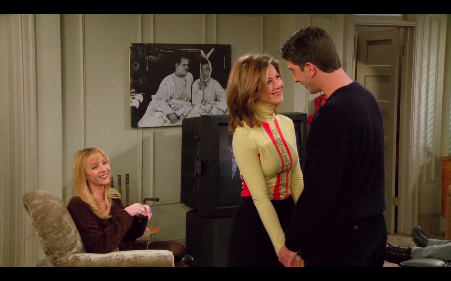 Jennifer Aniston as Rachel Green in Friends wearing black shorts over tights and yellow and red rollneck top.