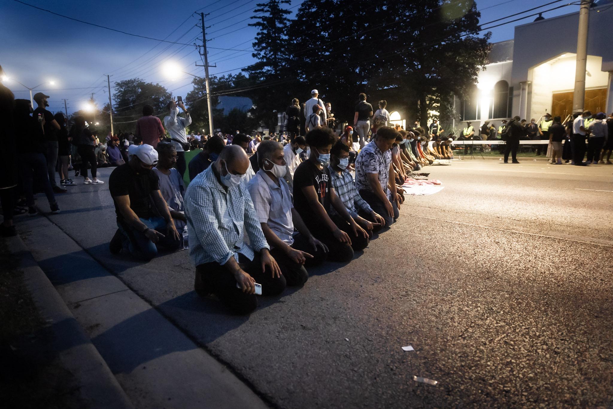 Community members pray outside the London Muslim Mosque.