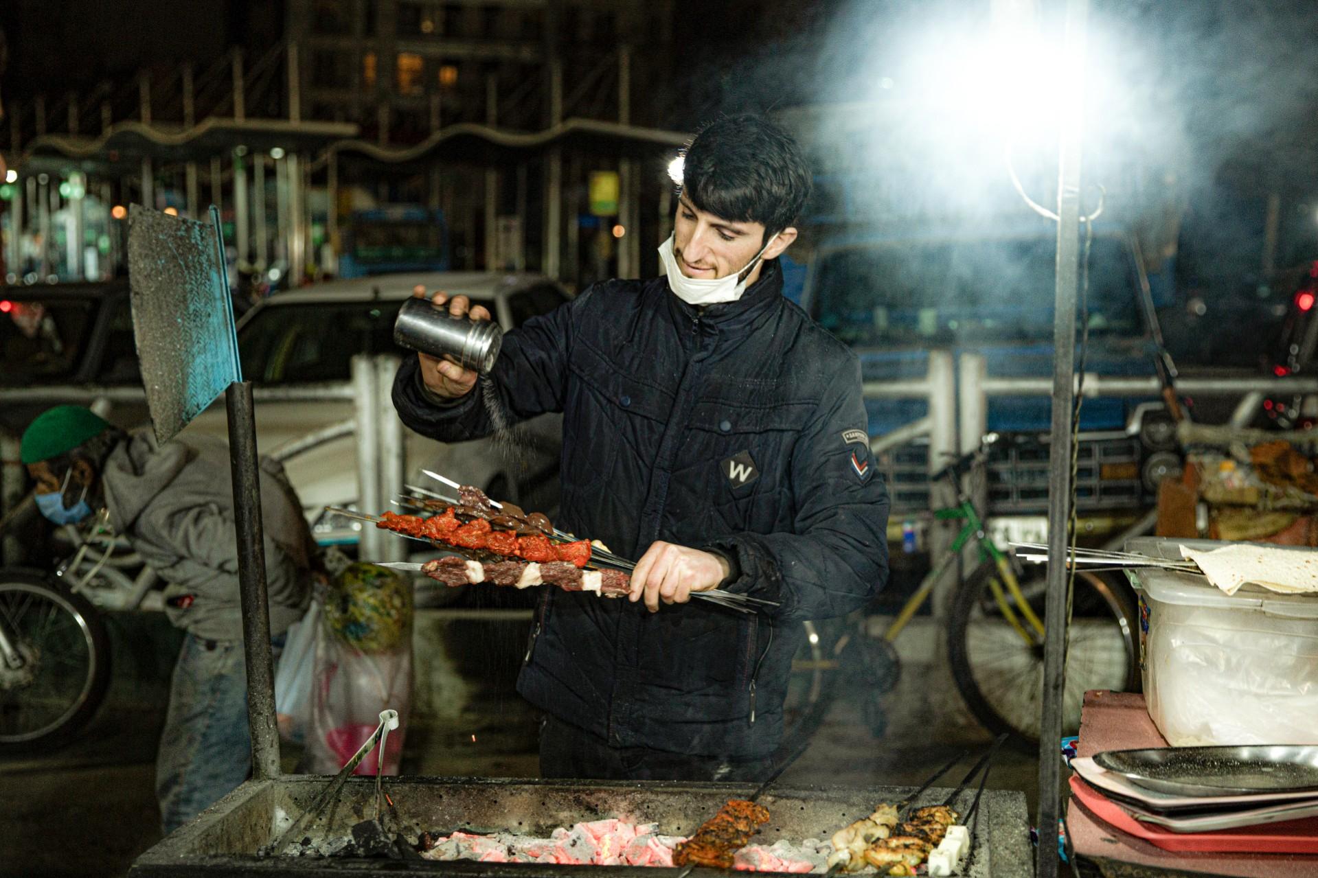 Pedagang sate menyiapkan makanan sambil membuka masker