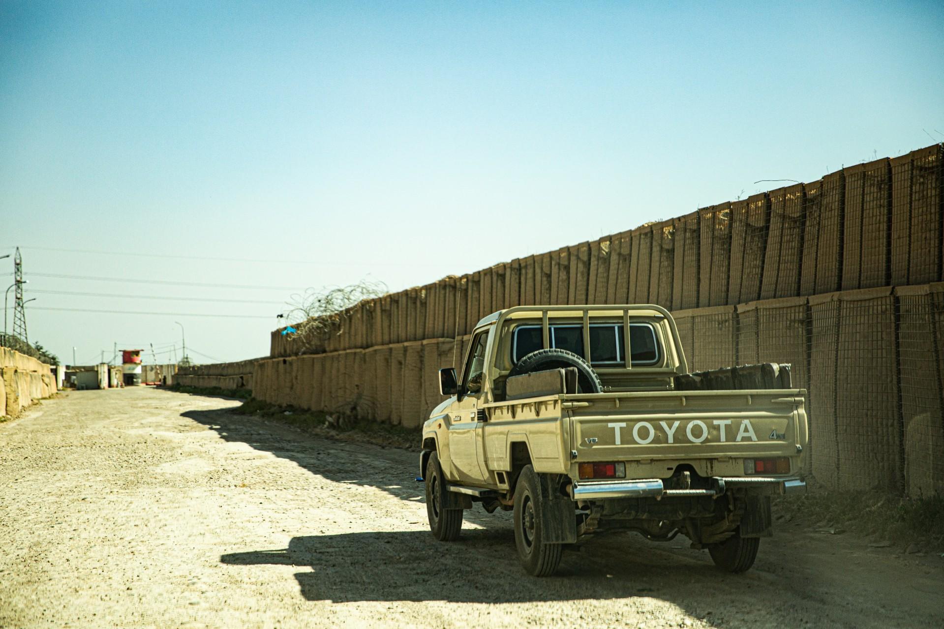 Mobil melewati jalanan bertembok di Irak.