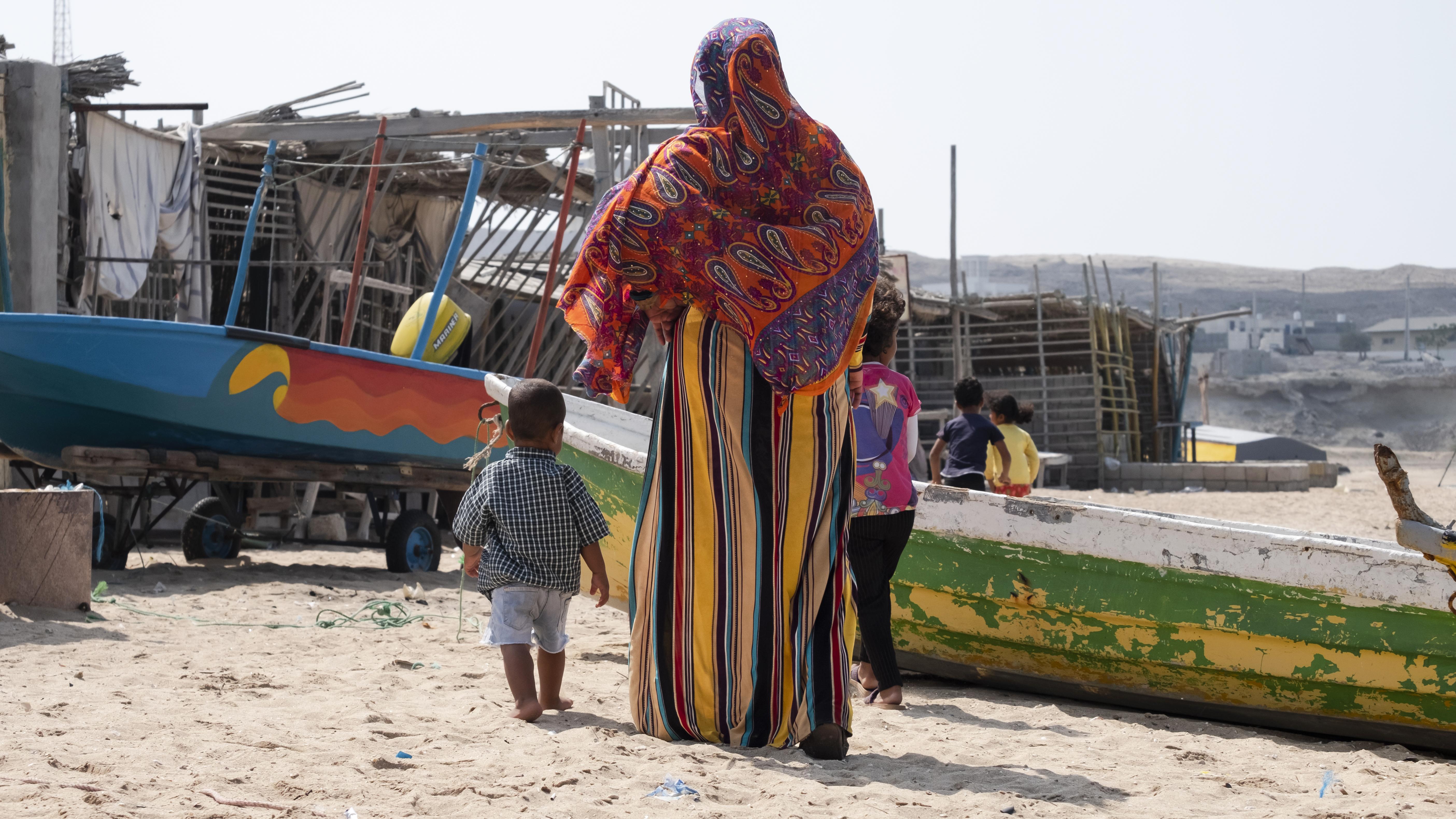 Nelayan perempuan berdiri di dekat kapal bersama anak laki-laki.