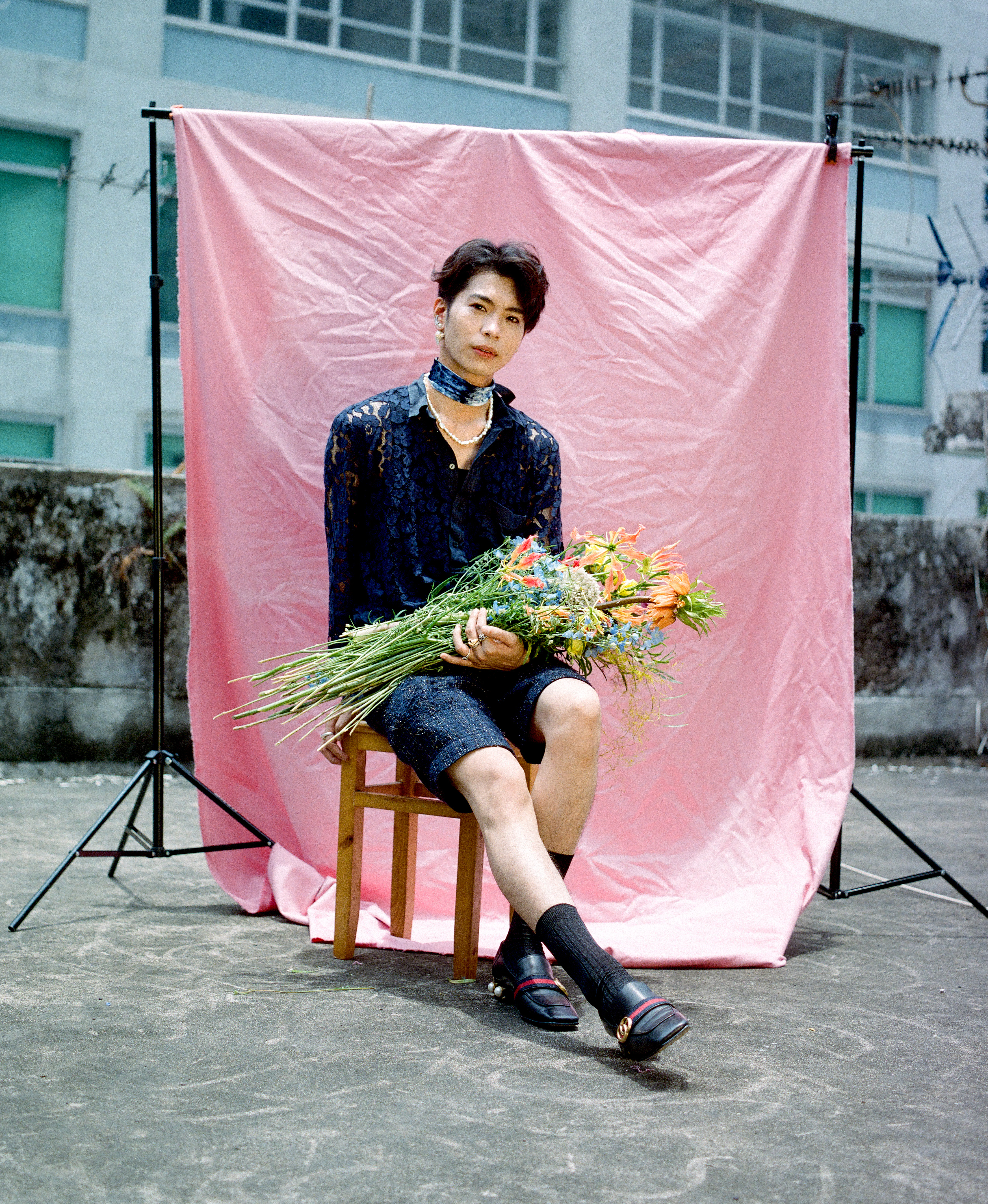 a portrait of mite sitting on a chair in front of a pink background and holding flowers