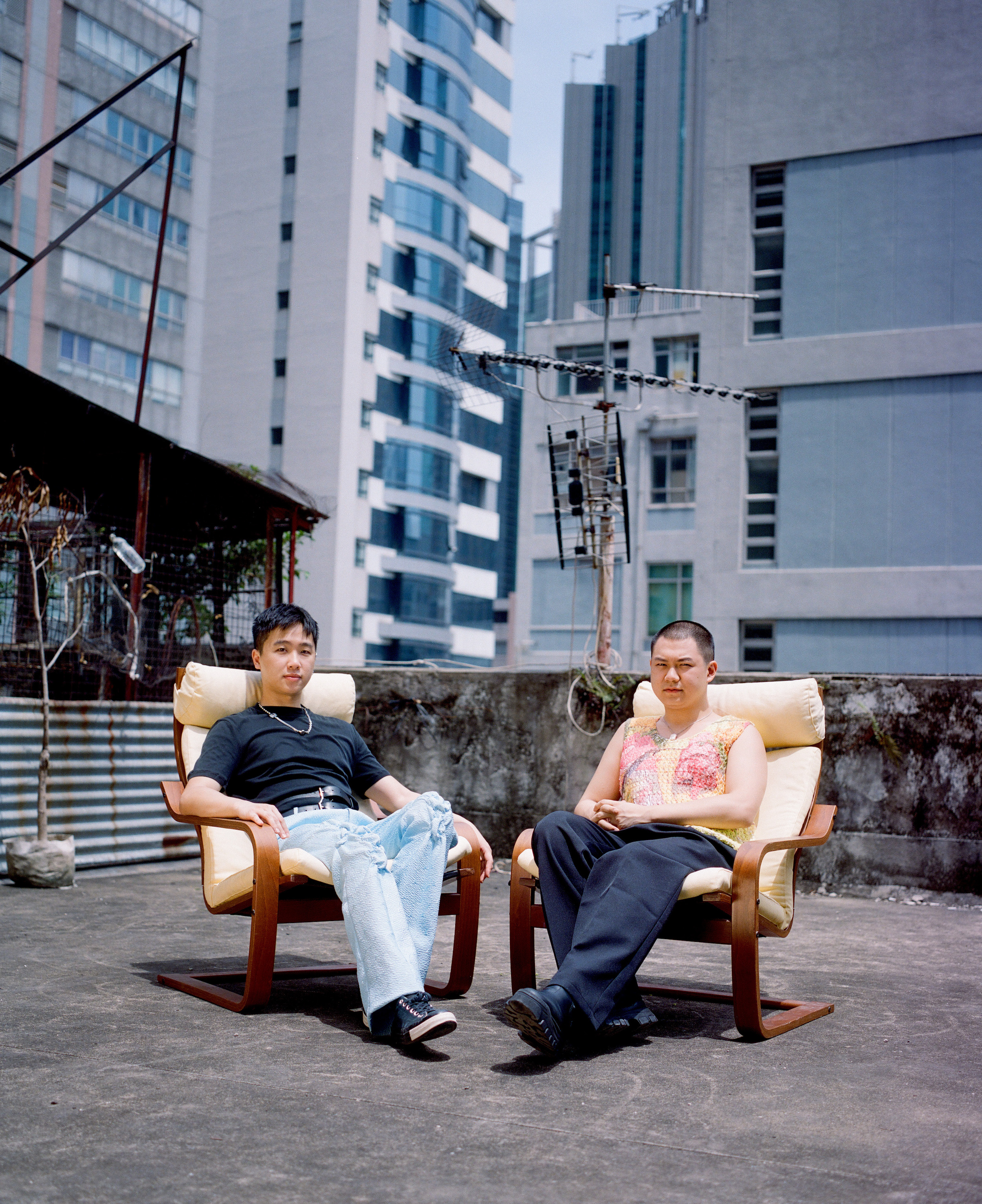 derek cheng and alex po sitting in chairs on a hong kong rooftop