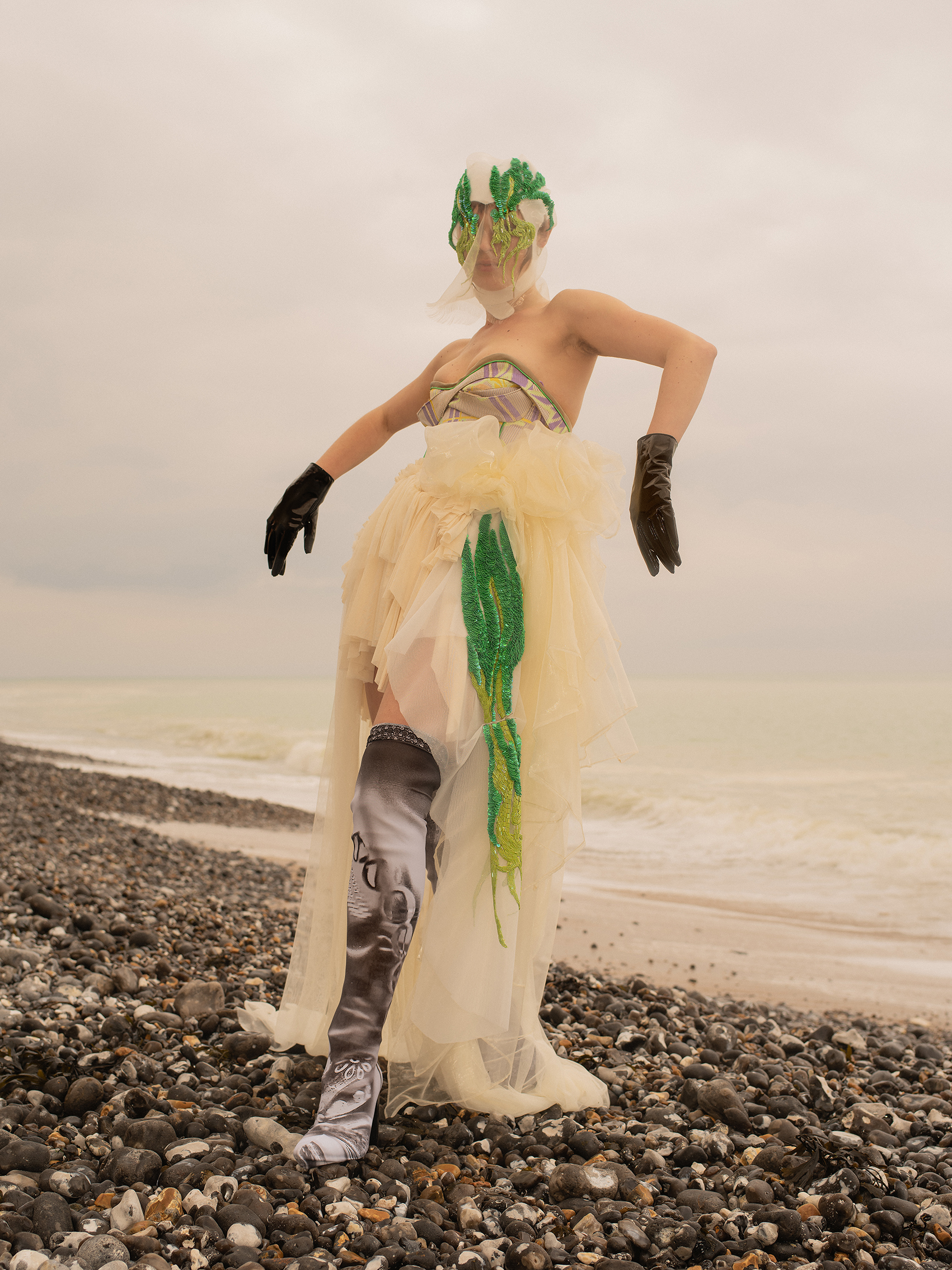A model on a rocky beach wearing a full look from Anna Deller-Yee's RCA MA graduate collection