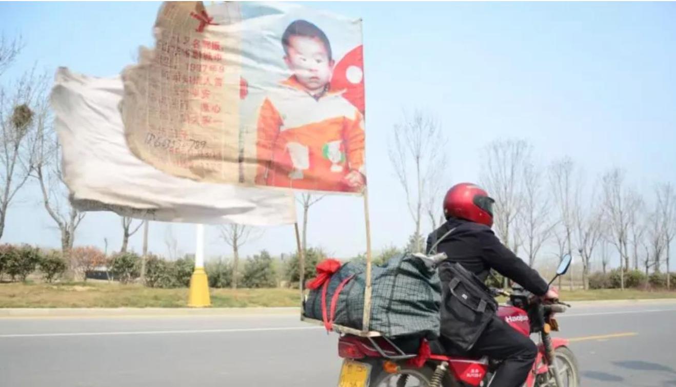 Guo mengendarai motor dengan spanduk besar berkibar di belakangnya Foto: CCTV