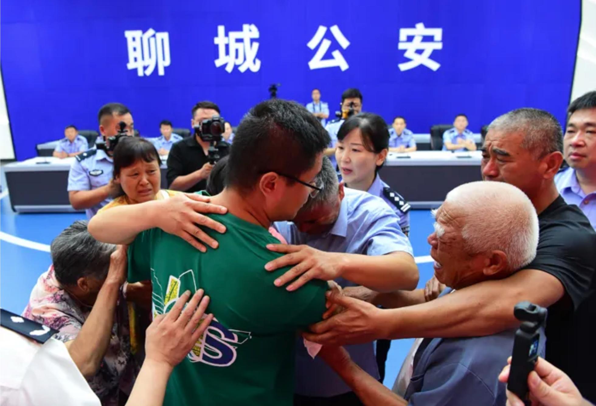 Guo Gangtang (lelaki tua yang memakai kemeja biru muda) berpelukan dengan putranya Guo Xinzhen (kaus hijau). Foto: Biro Keamanan Publik Liaocheng