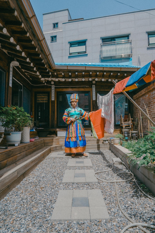 Lelaki mengenakan pakaian tradisional di depan bangunan kecil.