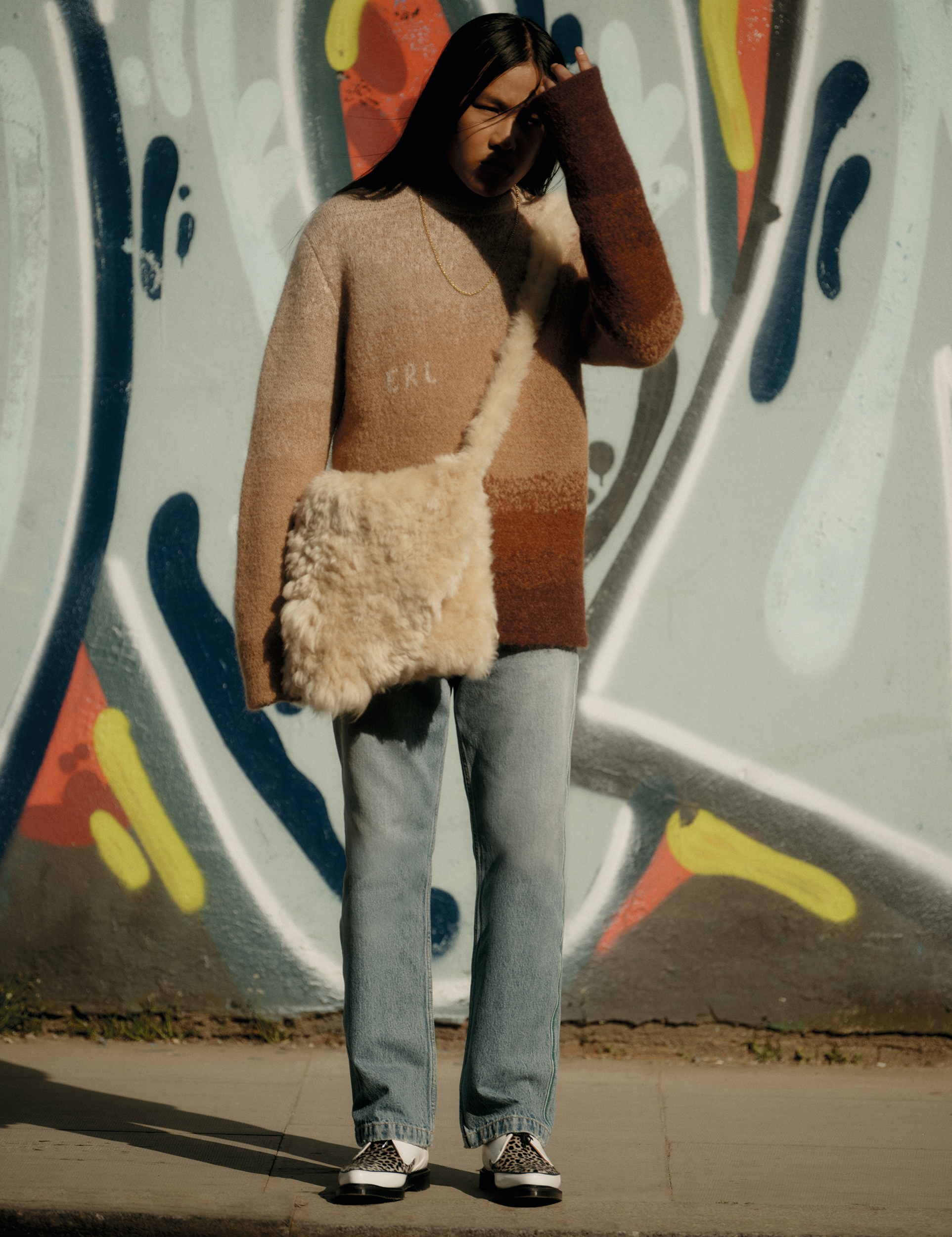 a model standing against a graffiti wall wearing a sweater, jeans and a fluffy shoulder bag