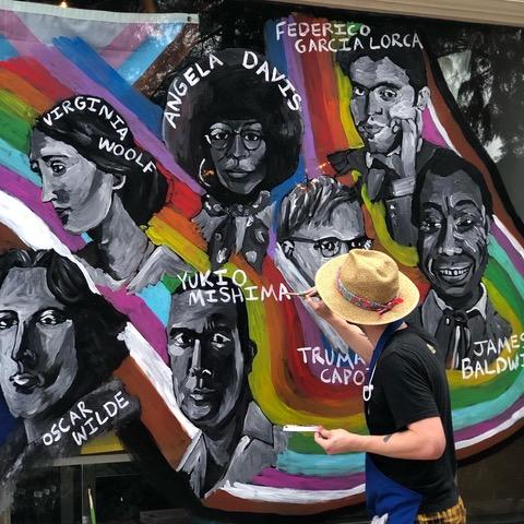 A Pride mural of LGBTQ+ authors featured in Beausoleil storefront window painted by local artist Benjamin Koch