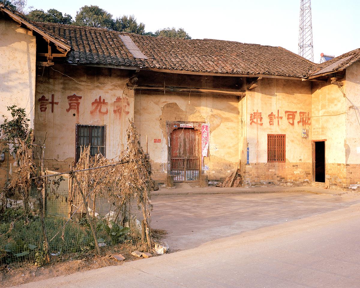 Gedung tua dengan tulisan berwarna merah dalam bahasa Mandarin