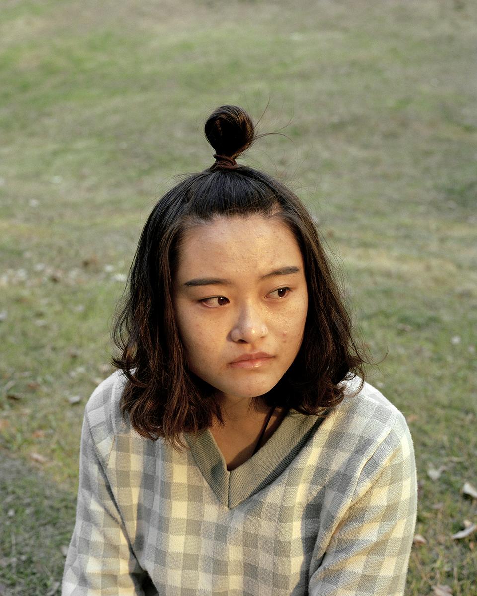 Remaja perempuan dengan rambut cepol mengenakan atasan kotak-kotak