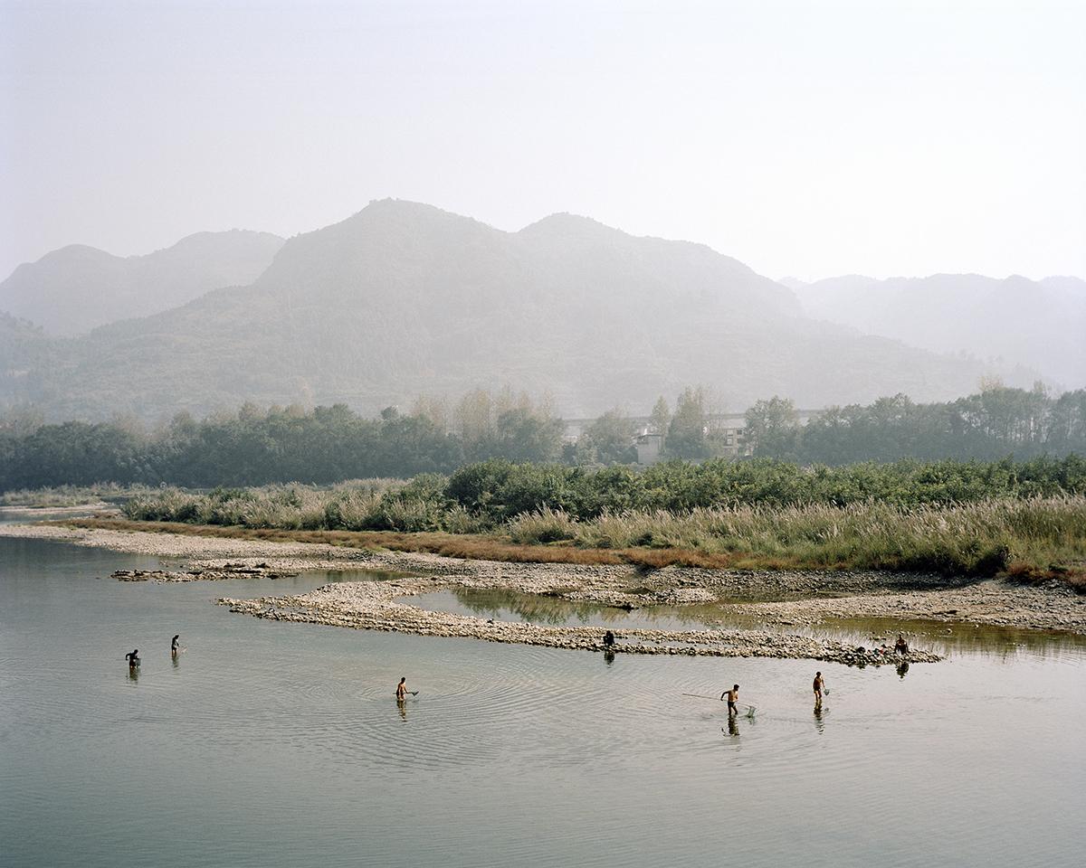 Nelayan mencari ikan di kali, pegunungan membentang di belakang mereka.