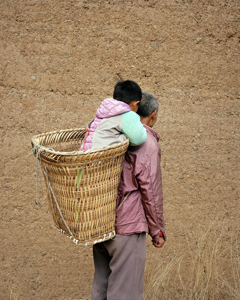 Lelaki tua menggendong anak laki-laki di atas bakul.