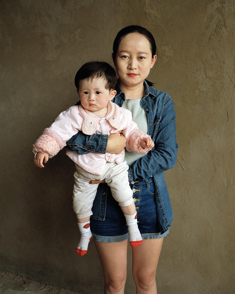 Perempuan muda yang mengenakan jaket jins sedang menggendong anak