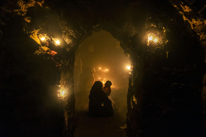 Pengunjung berdoa di lorong yang diterangi lilin