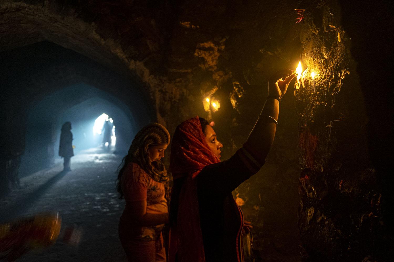 Dua perempuan menyalakan lilin di lorong