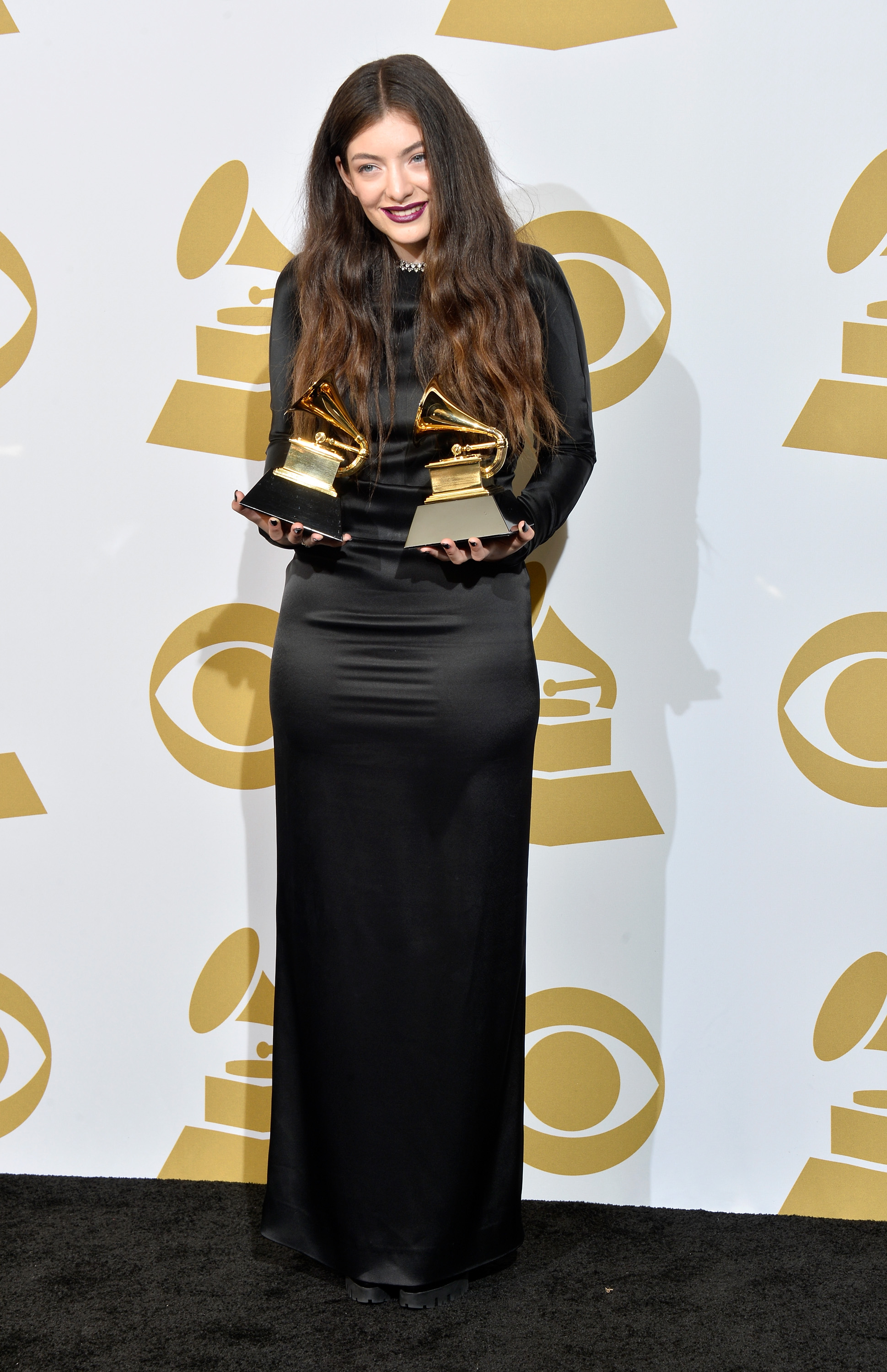 lorde holding up two grammy awards in a black column dress 2014