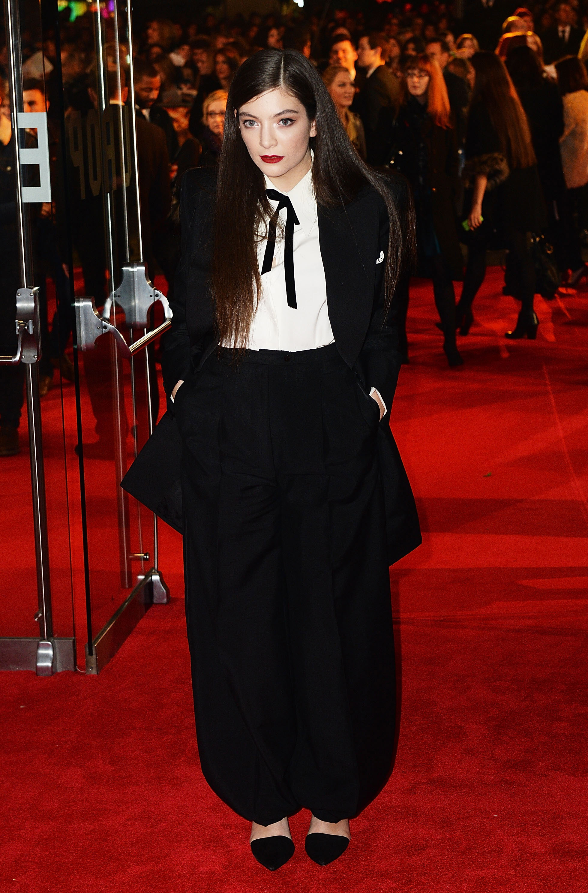 lorde posing on the red carpet with her hands in her pockets 2014