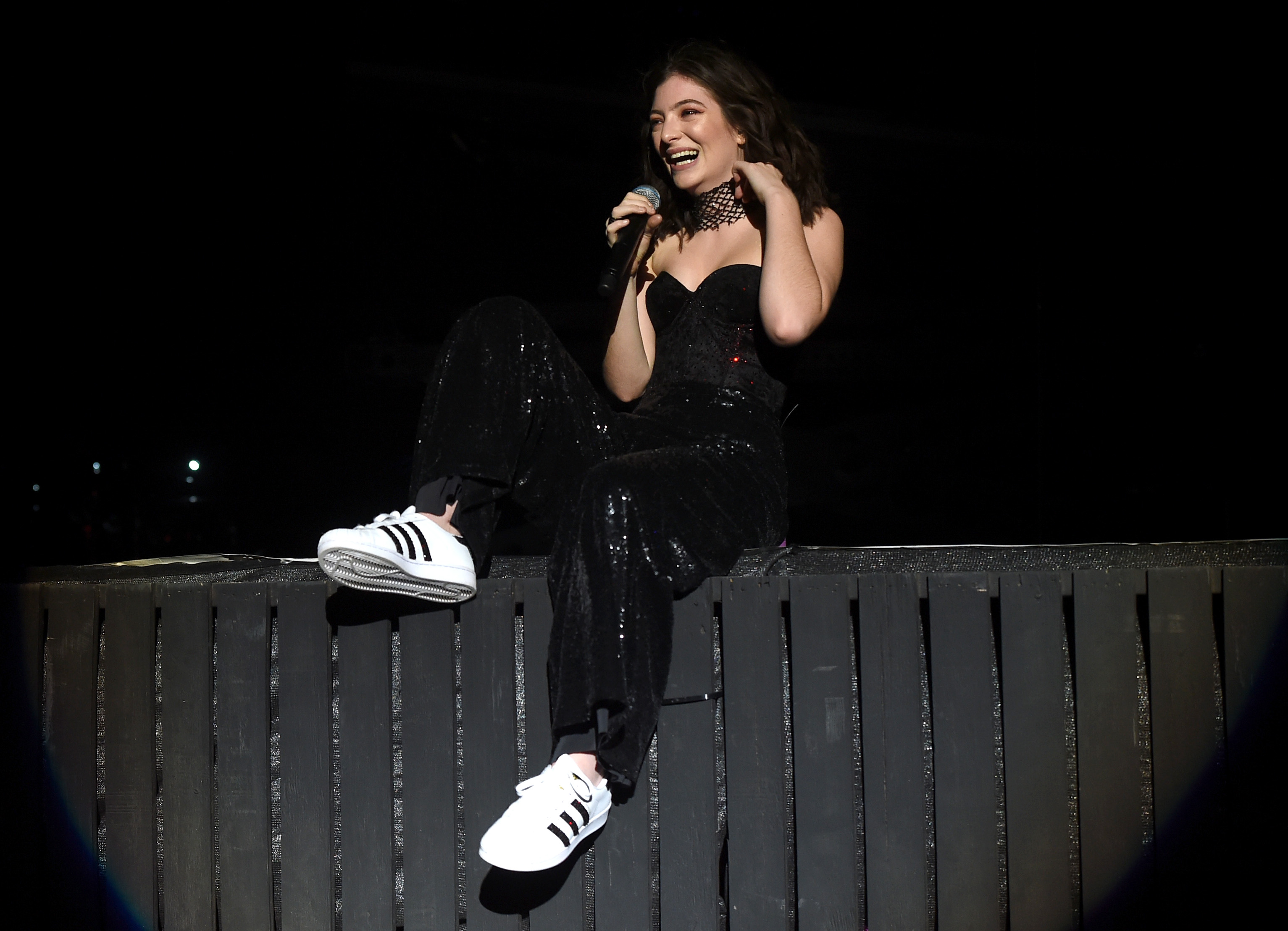lorde sitting on top of a fence singing at coachella 2017