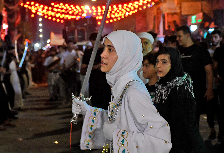 Perempuan mengangkat pedang di upacara berkabung yang digelar di Nasiriyah. Foto: Asaad Niazi/AFP via Getty Images