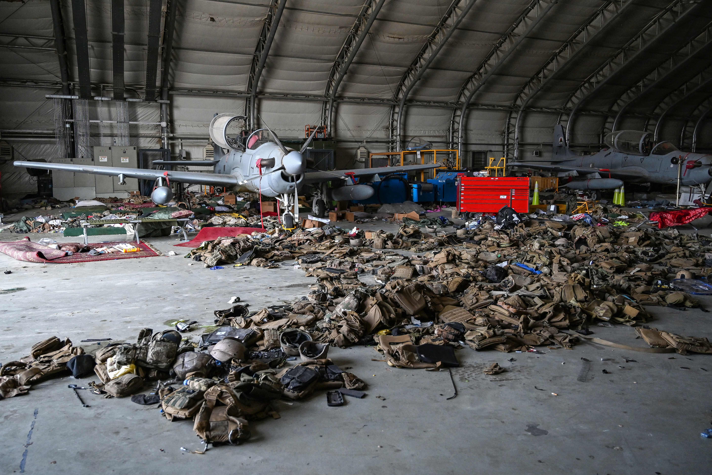 Pesawat serang Angkatan Udara Afghanistan diistirahatkan di hanggar bandara Kabul. Tumpukan rompi militer tersebar di sekitarnya. Foto oleh Wakil Kohsar/AFP via Getty Images