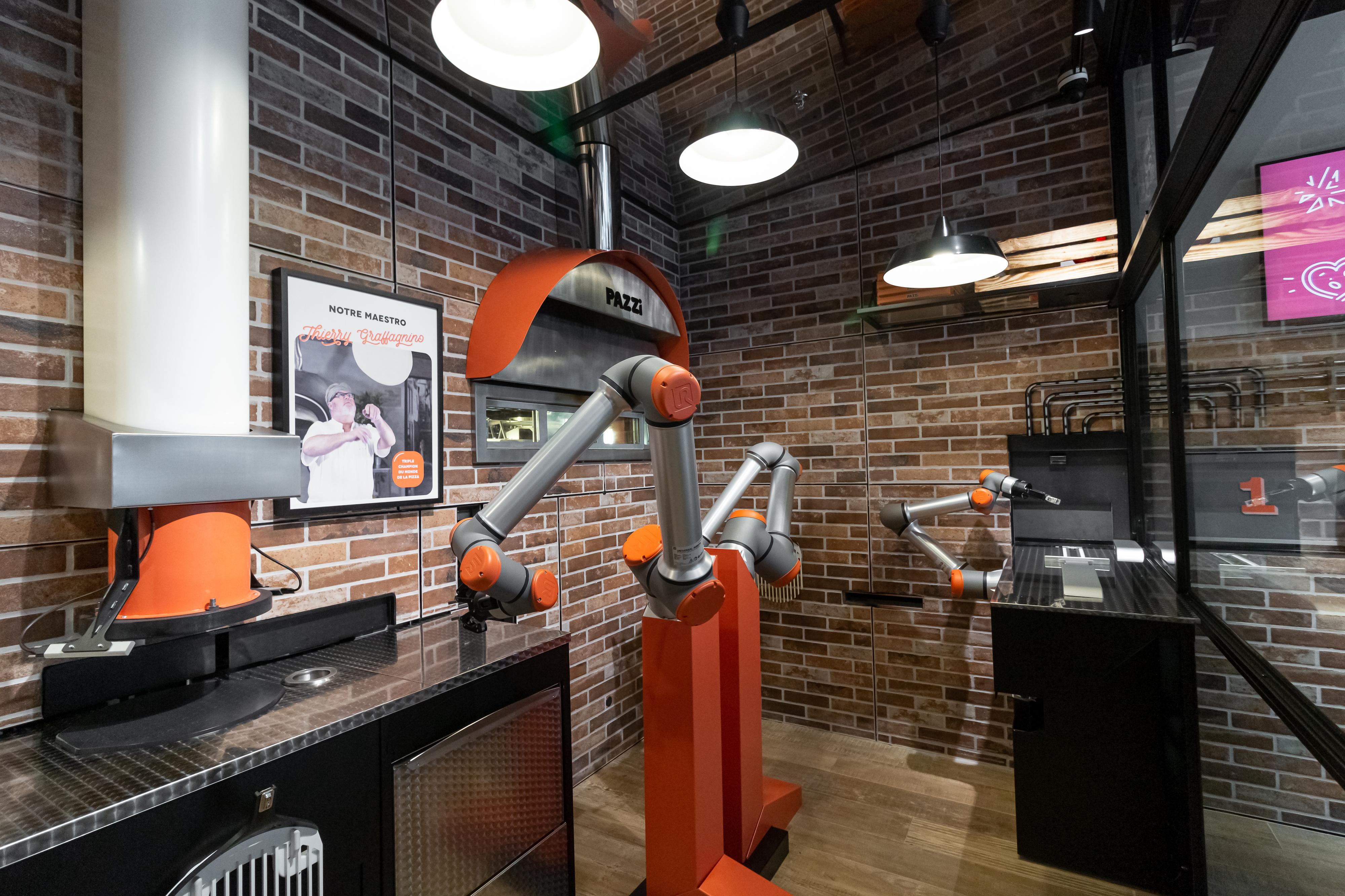 Robot berbentuk sepasang tangan besi perak dan sepasang kaki merah di dapur