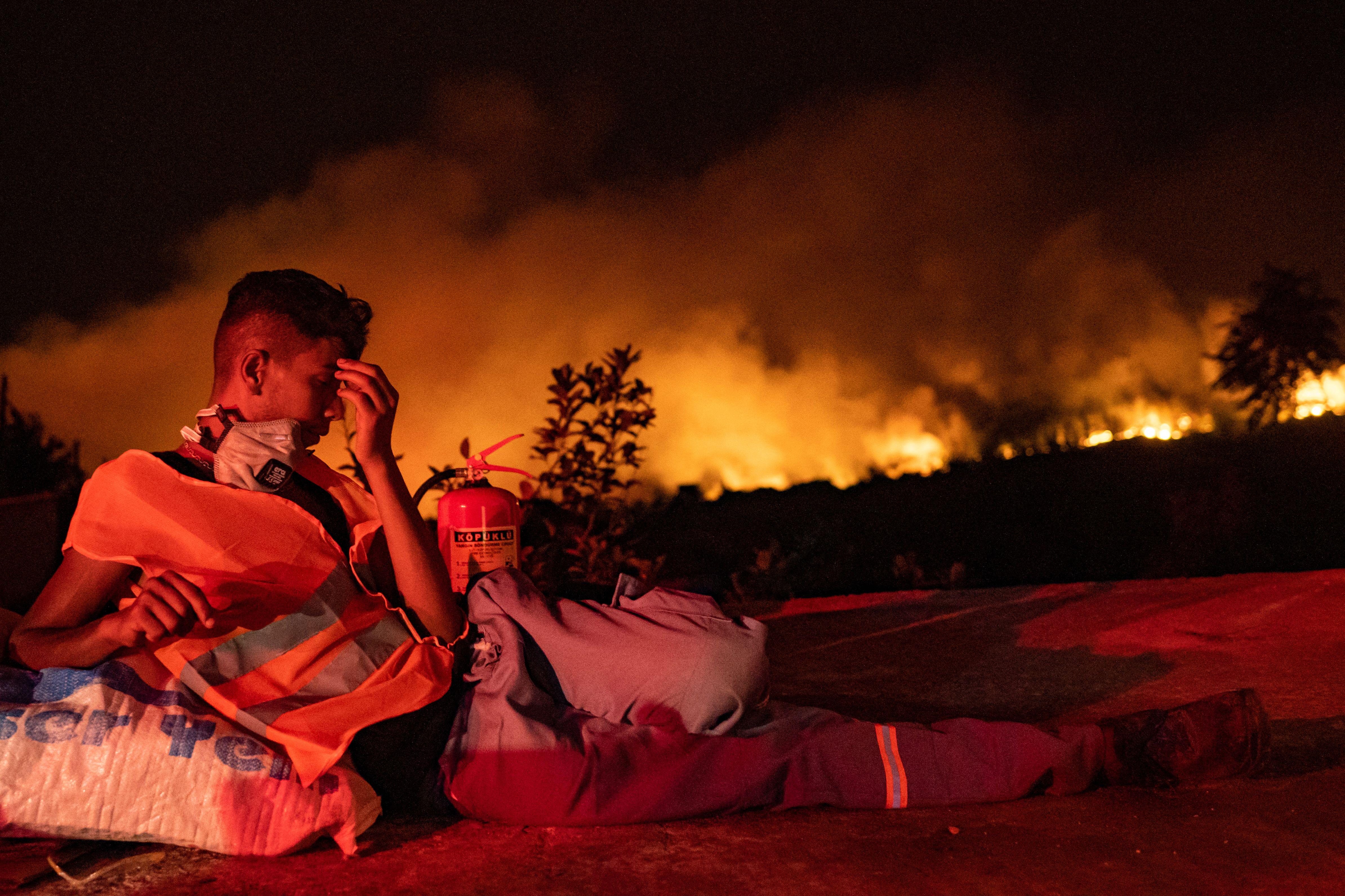 Sukarelawan beristirahat di tengah kobaran api yang melahap hutan provinsi Mugla di Turki bulan lalu. Foto: Yasin Akgul/AFP via Getty Images