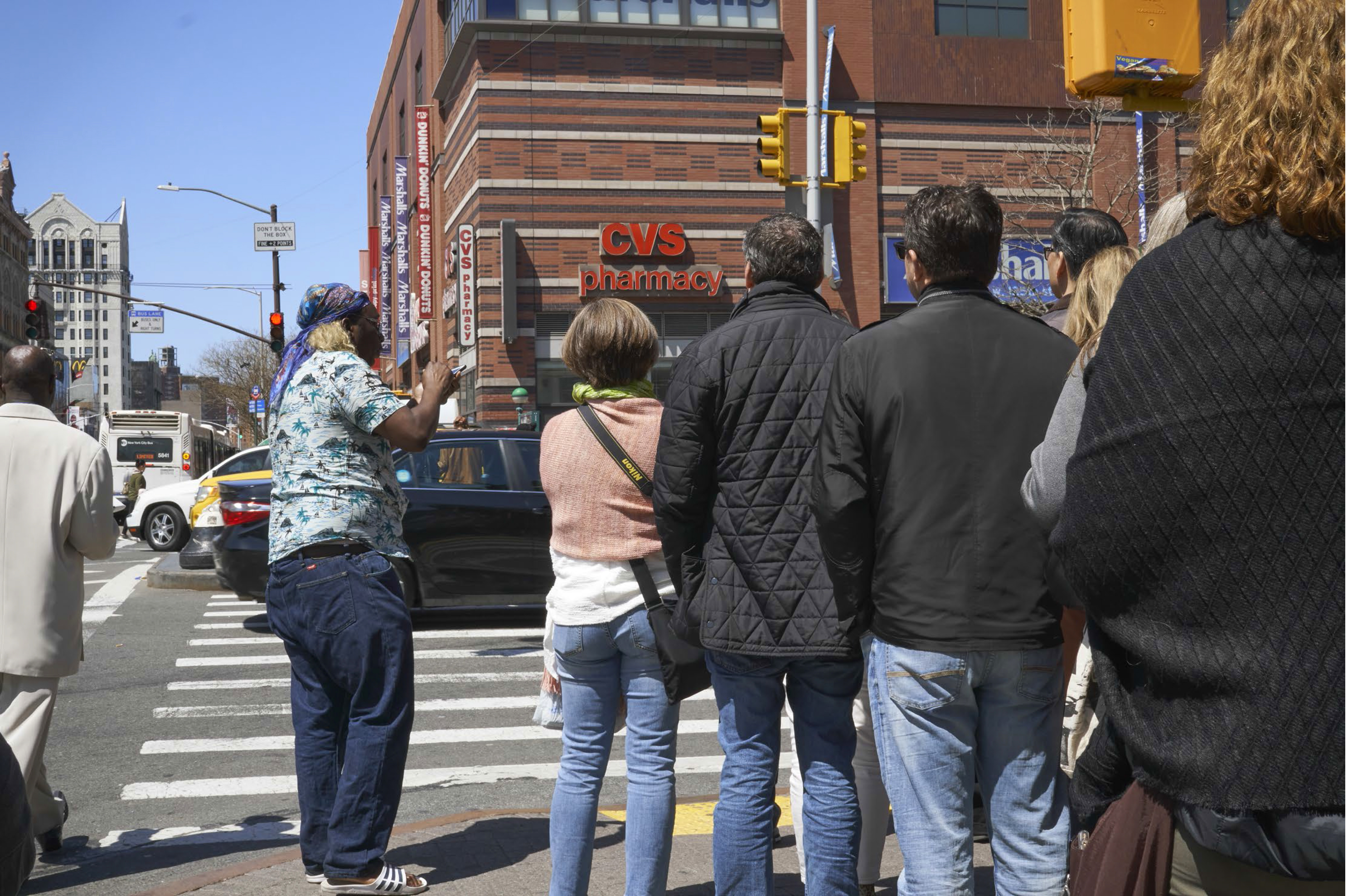 a man stands on the sidewalk near a railway crossing and talks to strangers walking past