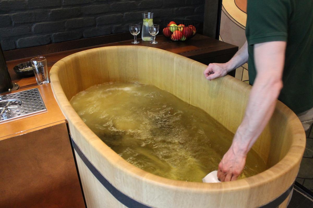 Petugas spa menuangkan bahan-bahan bir ke dalam rebusan air.