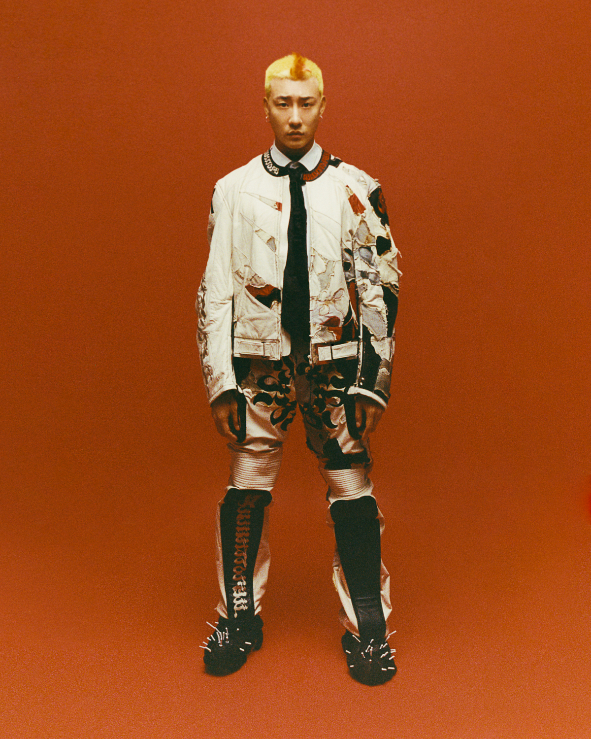 a portrait of a person with bleached hair wearing a worn leather biker jacket against a red background