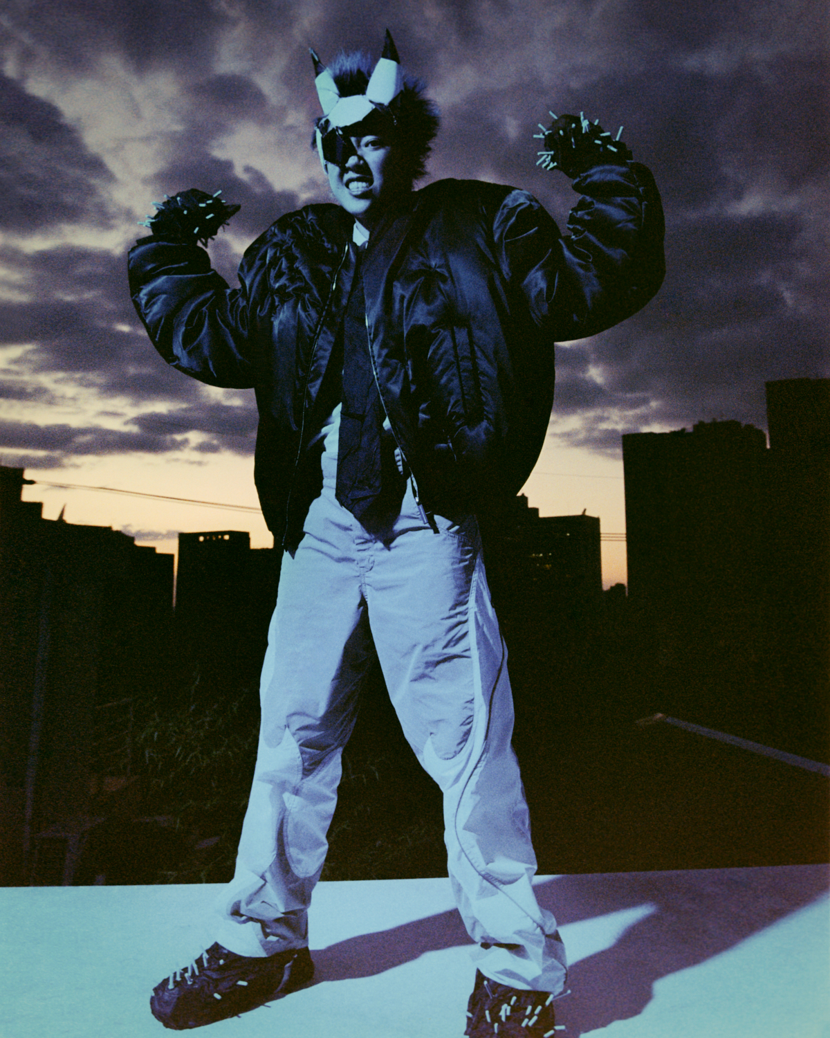 a photograph of a person wearing an eye patch, devil horns and a bomber jacket, standing on a roof at night, flexing their muscles