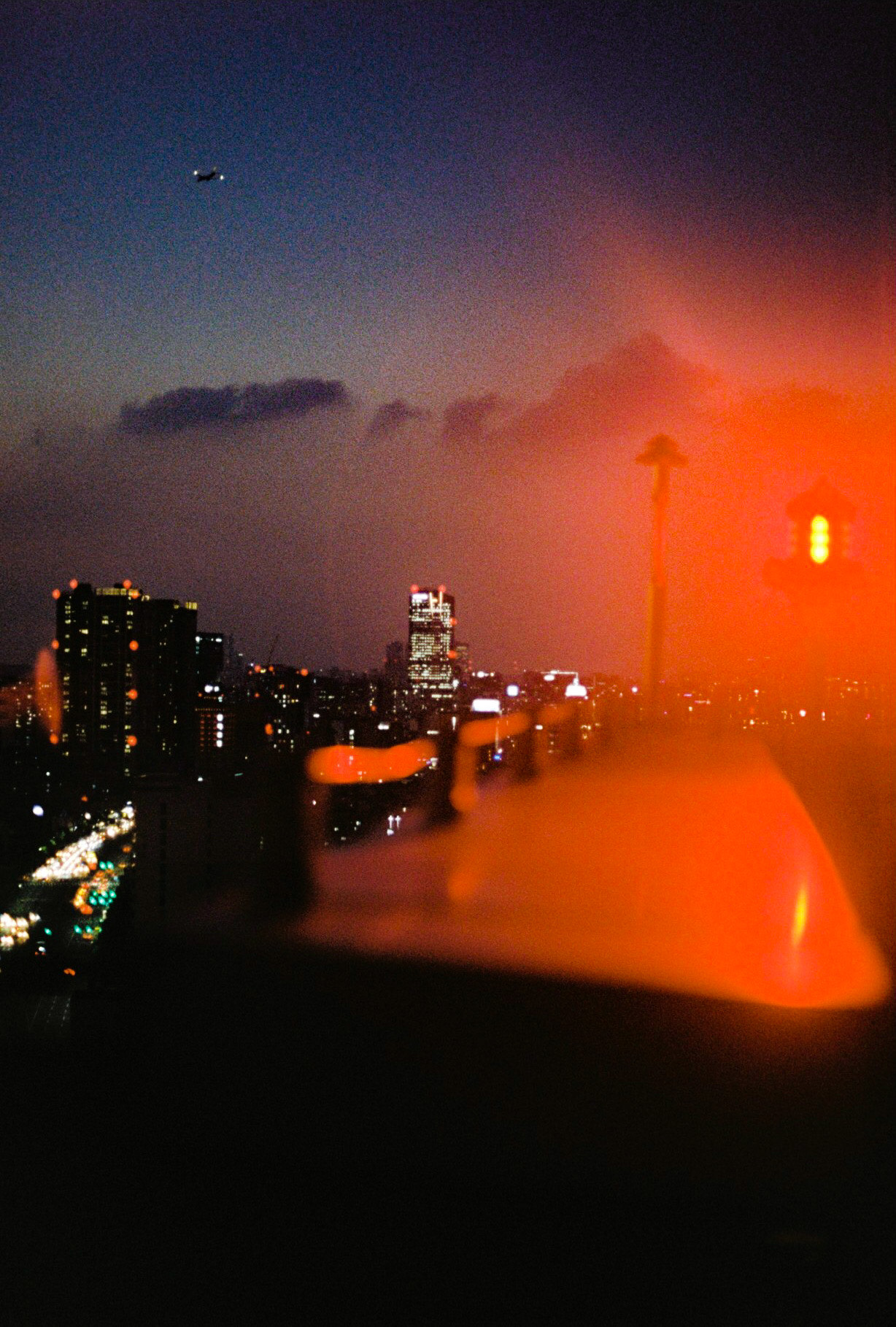 view of Seoul city skyline at night, the buildings and road lit up and highlighted by the flares of a red plane signal light.