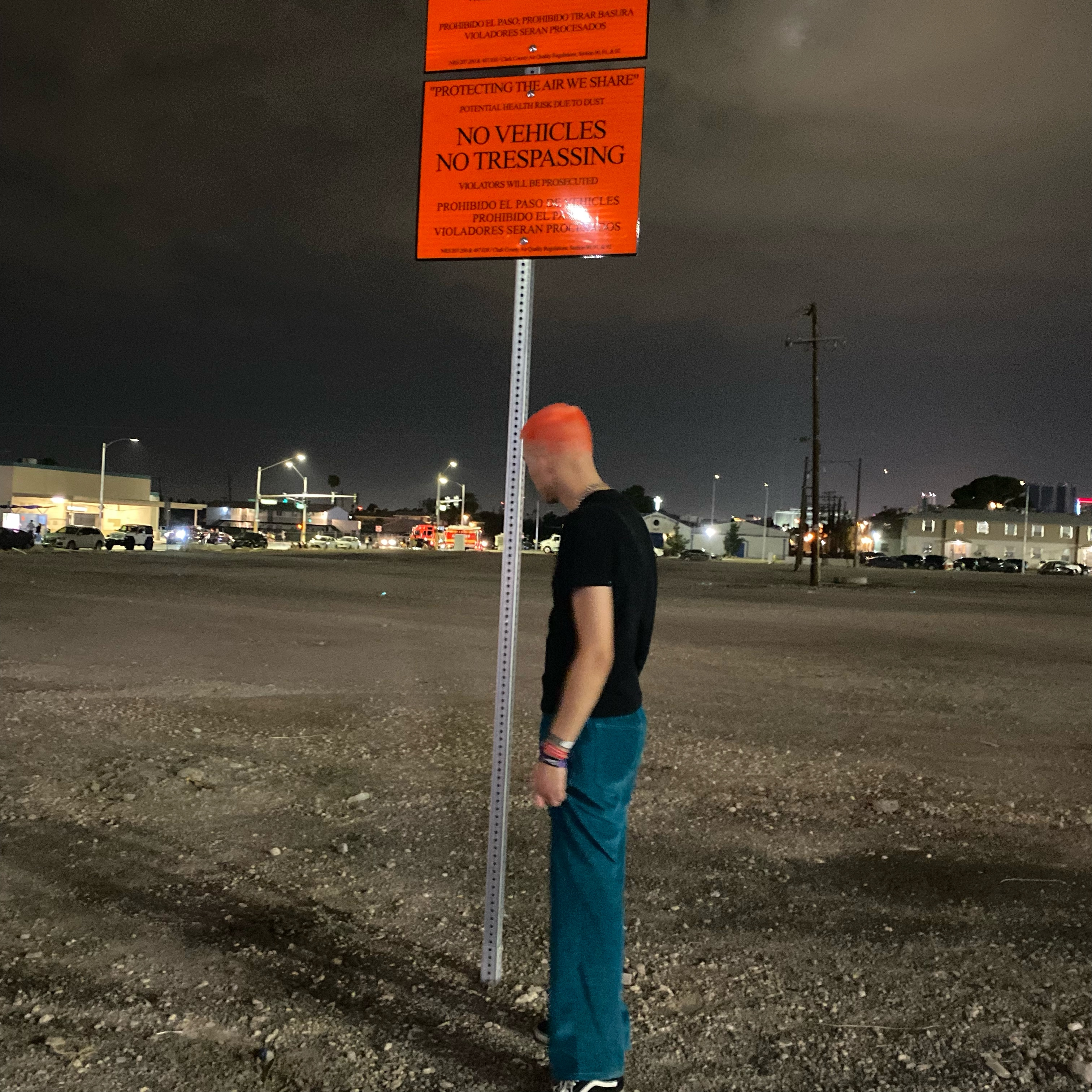 A man stands in front of a sign saying no vehicles no trespassing in the middle of a barren space at night.