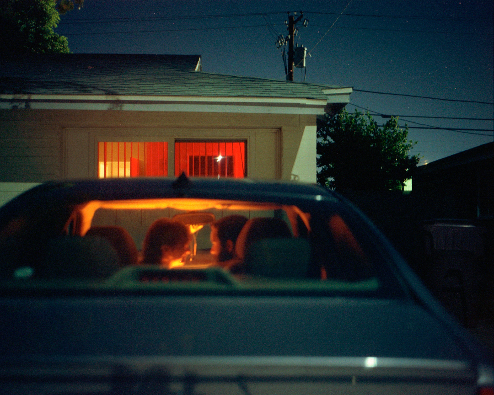 A couple sit in the front seats of a car parked in front of a house staring into each others eyes.