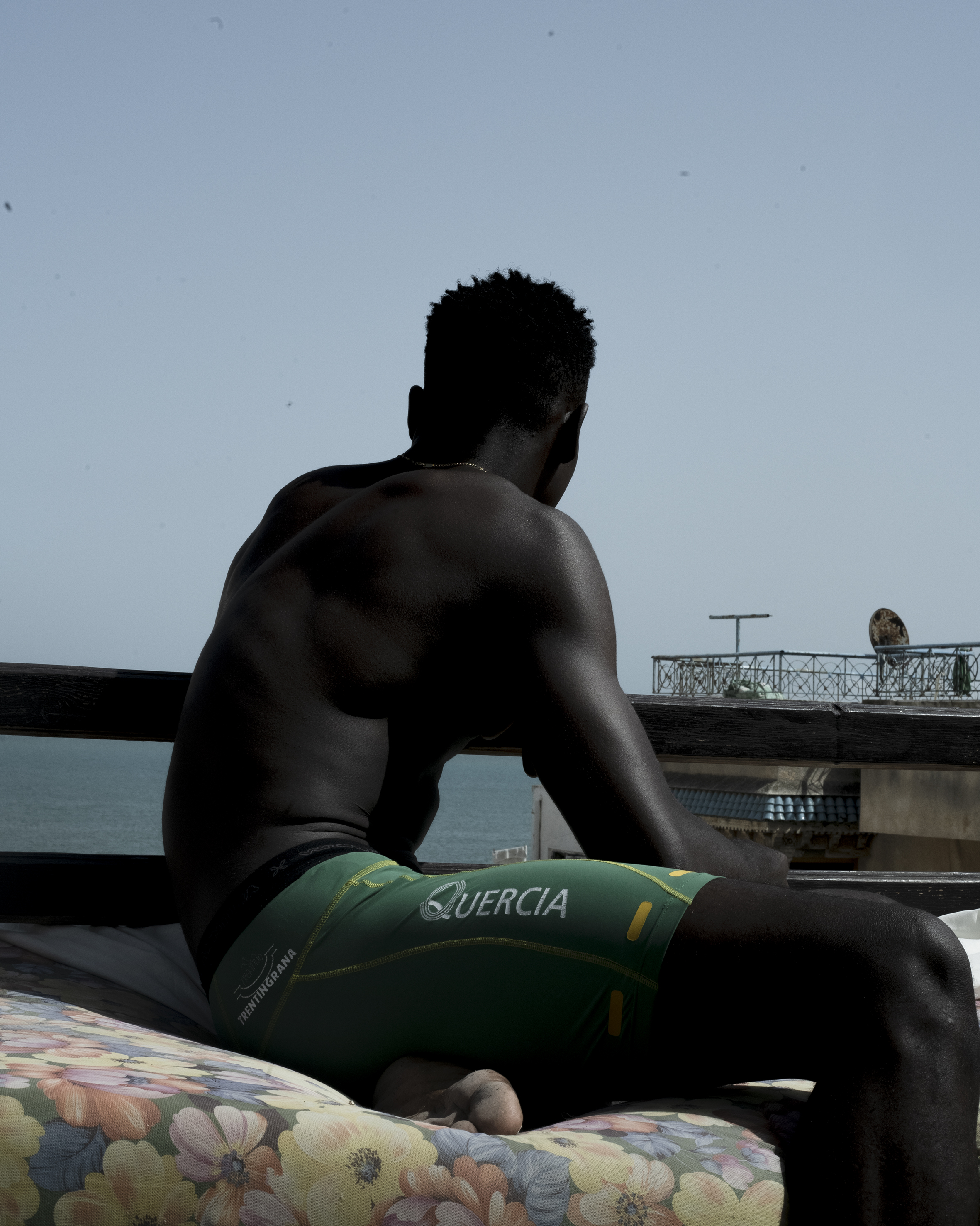 Man in shorts and shirtless sits on a floral cushion on a rooftop overlooking the ocean.