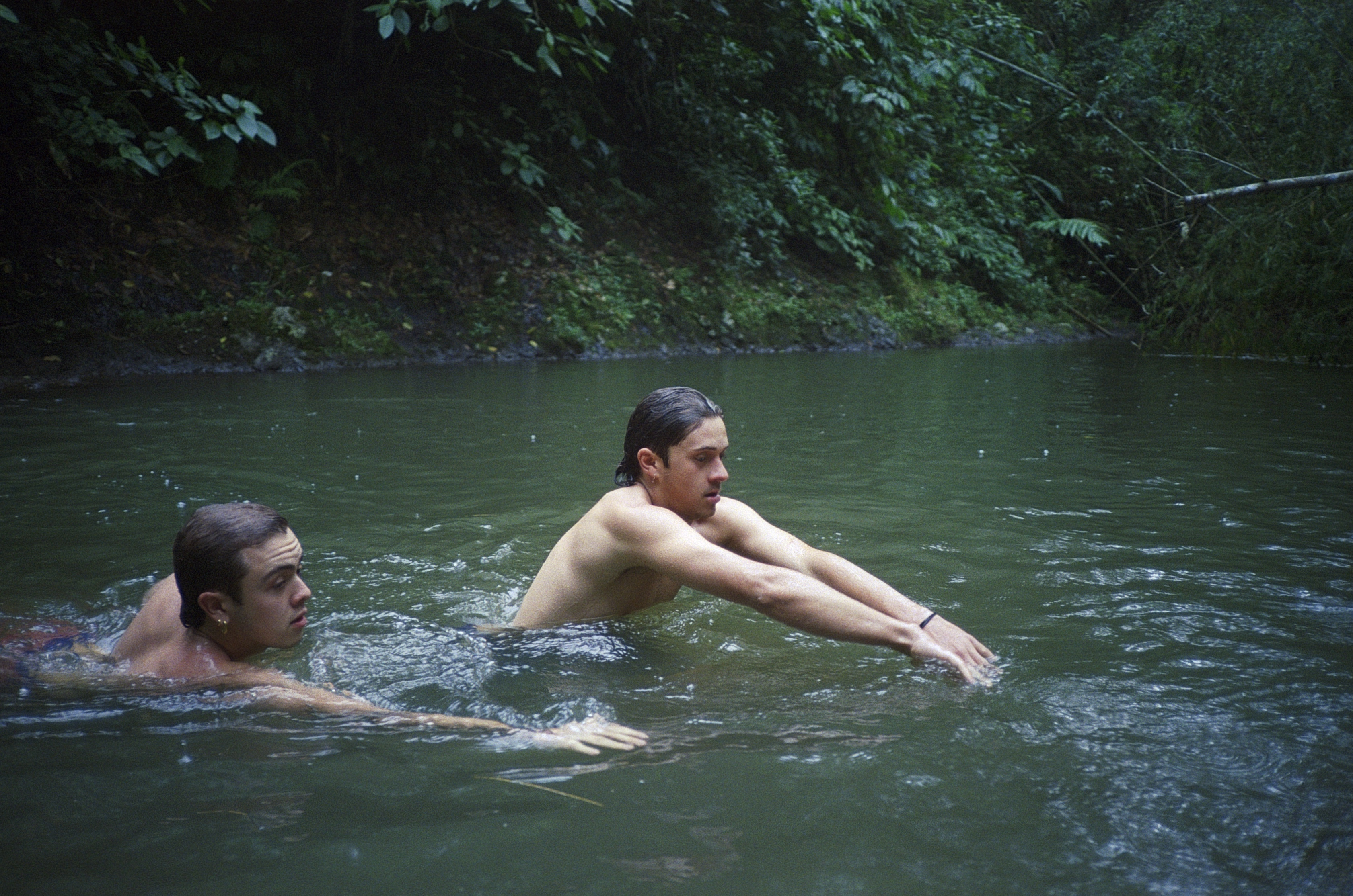 Two boys swim in a lake surrounded by trees