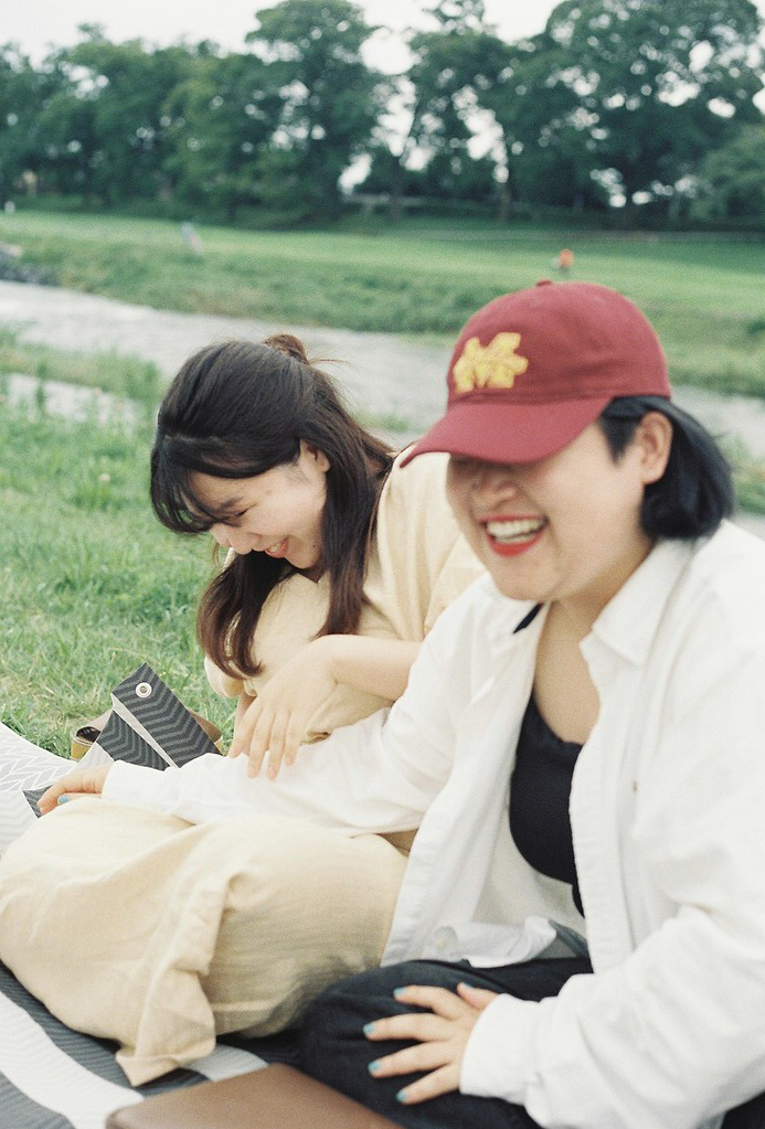 Two friends laugh sitting in the park