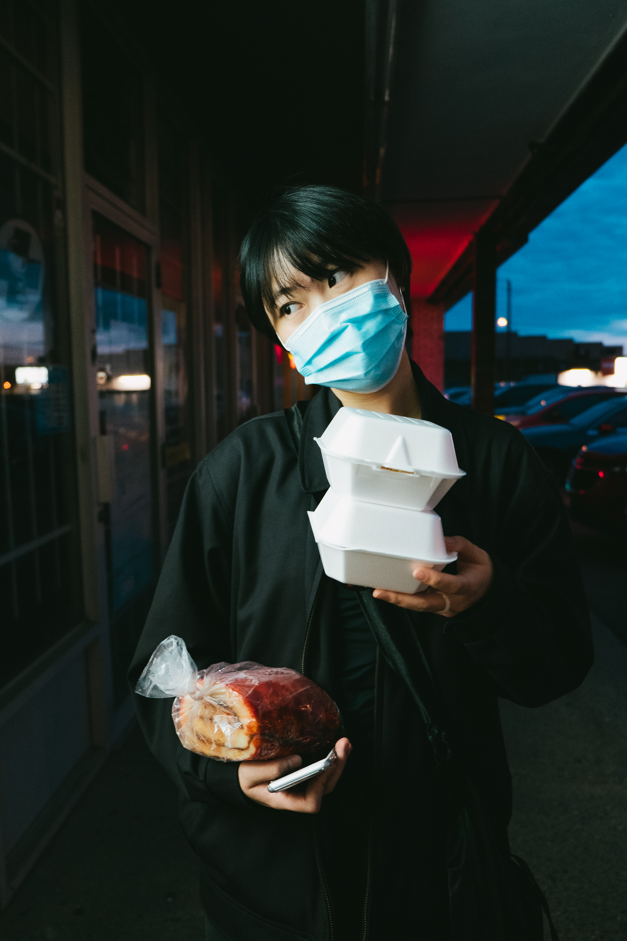 A girl wearing a mask walks along shop fronts at night carrying takeaway containers, a guava roll and her phone