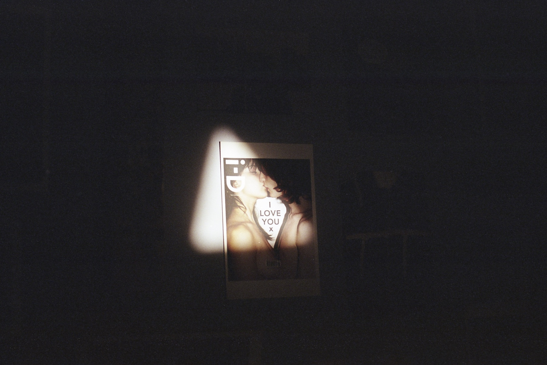 Poster of an i-D magazine cover against a blank wall and lit by a triangle of light.